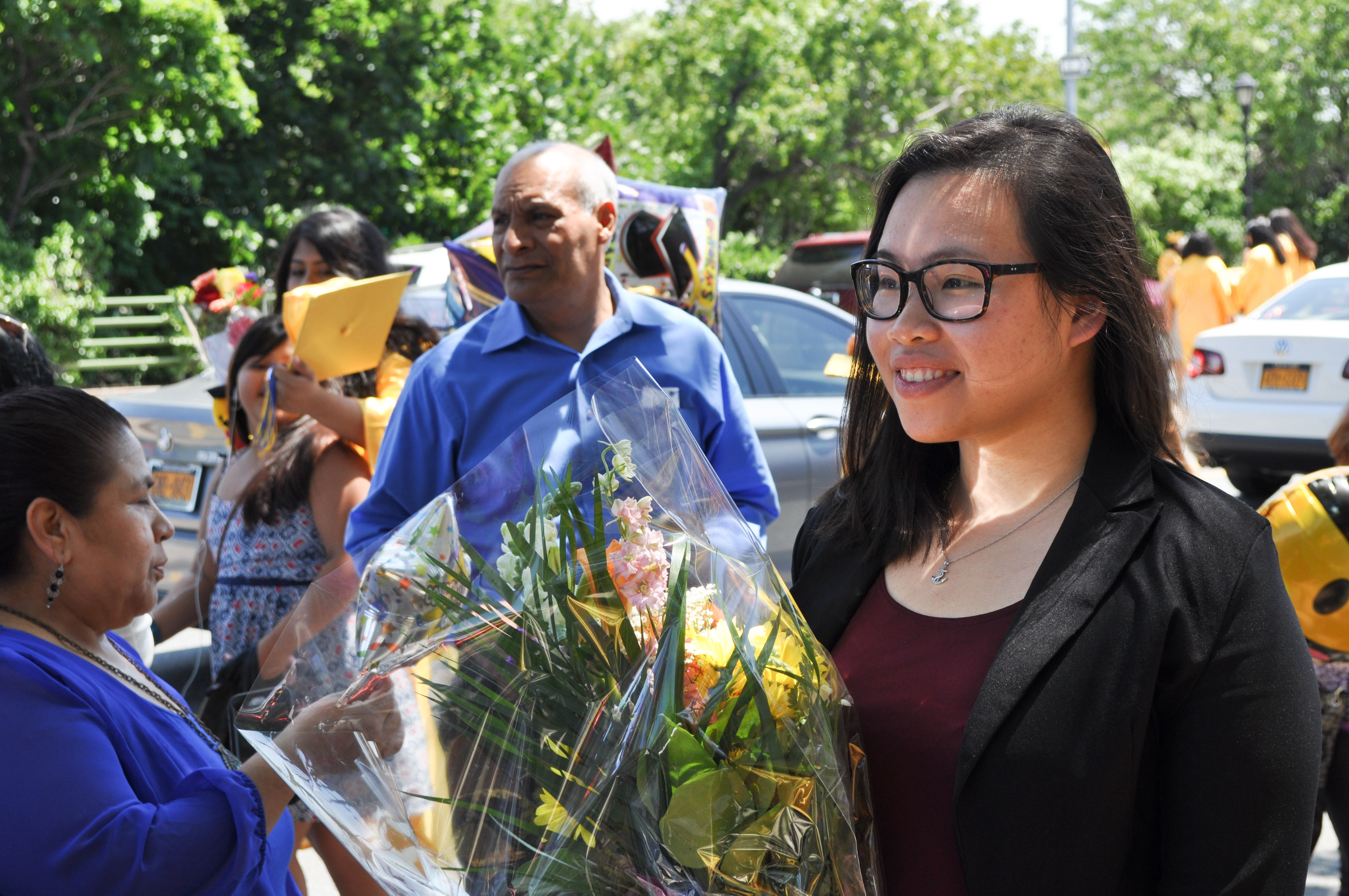 Qingmei Wu looks on as M.S. 88 students and parents gather for pictures after the graduation ceremony on Wednesday morning.