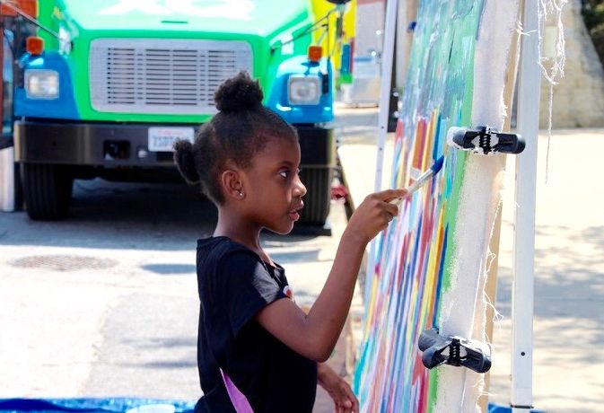 Gabrielle Colburn, 7, adds her artistic flair to a mural in downtown Memphis in conjunction with the XQ Super Schools bus tour in June. (Caroline Bauman)