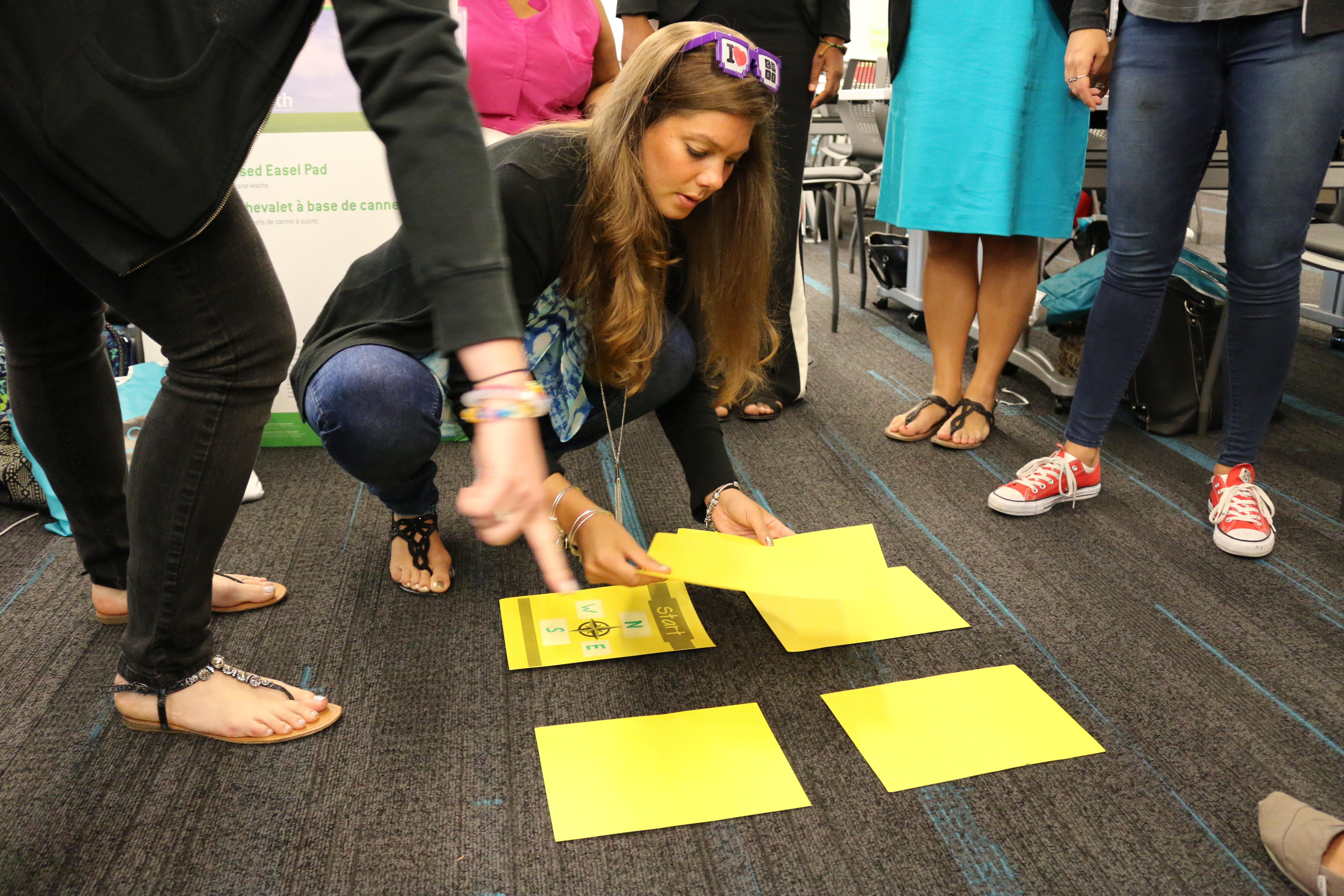 """A teacher sets up the yellow tiles for the """"walker"""" and """"controller"""" activity at the city's workshop for computer science in elementary school."""