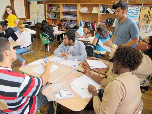 New Design High School social studies teacher Tad Donozo, right, helps coach 11th grade U.S. history students for next week's Regents exam.