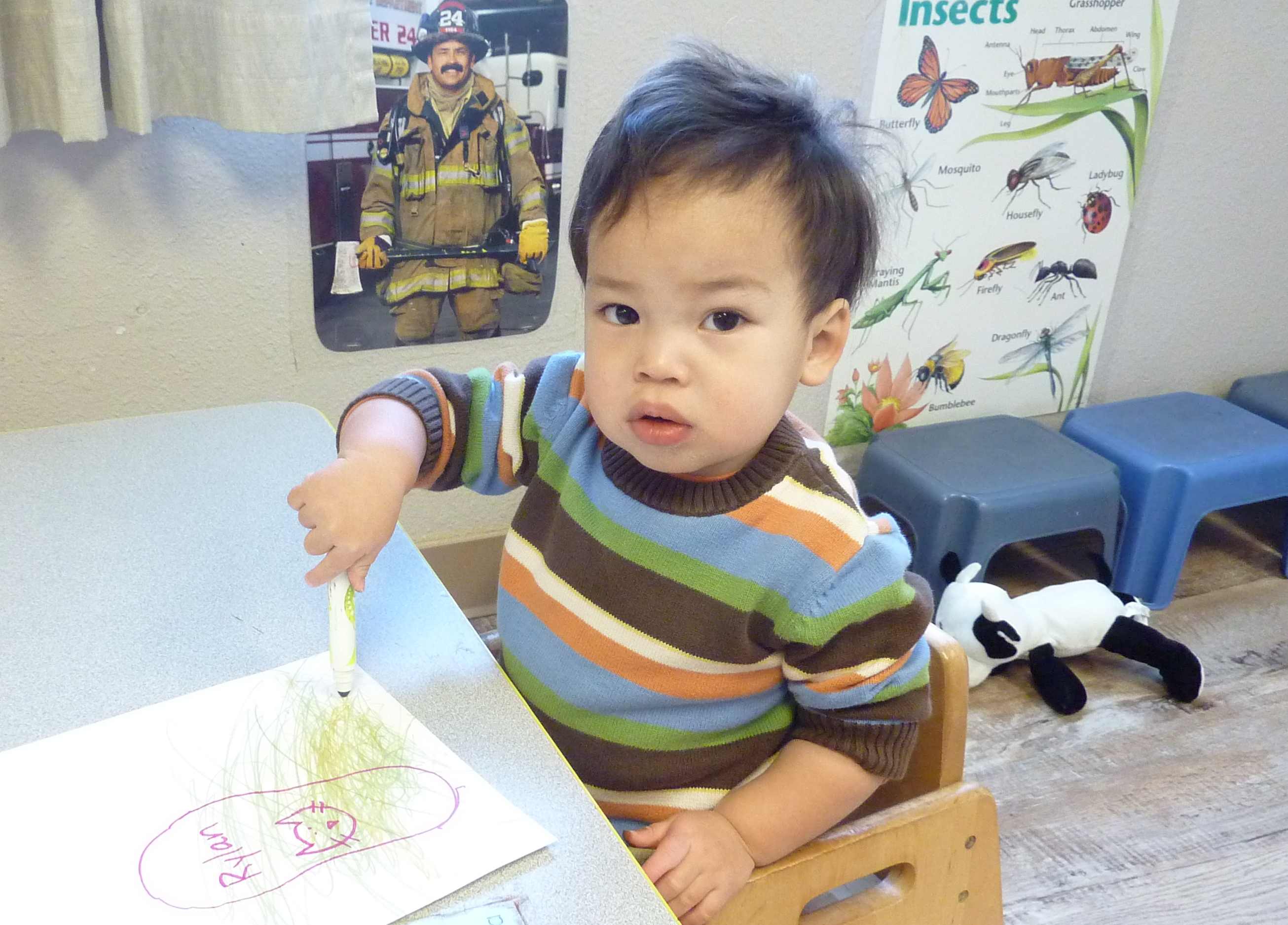A toddler at Loveland's Teaching Tree  Early Childhood Learning Center, draws on an outline of his foot.