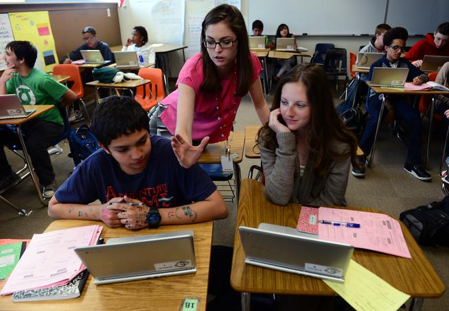 Algebra teacher Jessica Edwards helps students Yosef Abuharus, 14, left, and Emily Botkin, 14, right, with math problems during her 9th grade algebra class  at Smoky Hill High School last  year (Photo by Helen H. Richardson/ The Denver Post).