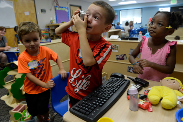 Max Gonzalez, 4, center, Gunnar Riley, 4, left, and Brooklyn Jones, 4, take turns looking through a camera as they spend part of their first week getting to know their new friends at Beck Preschool inside the Beck Recreation Center on August 29, 2017 in Aurora, Colorado. (Photo by Kathryn Scott/The Denver Post)