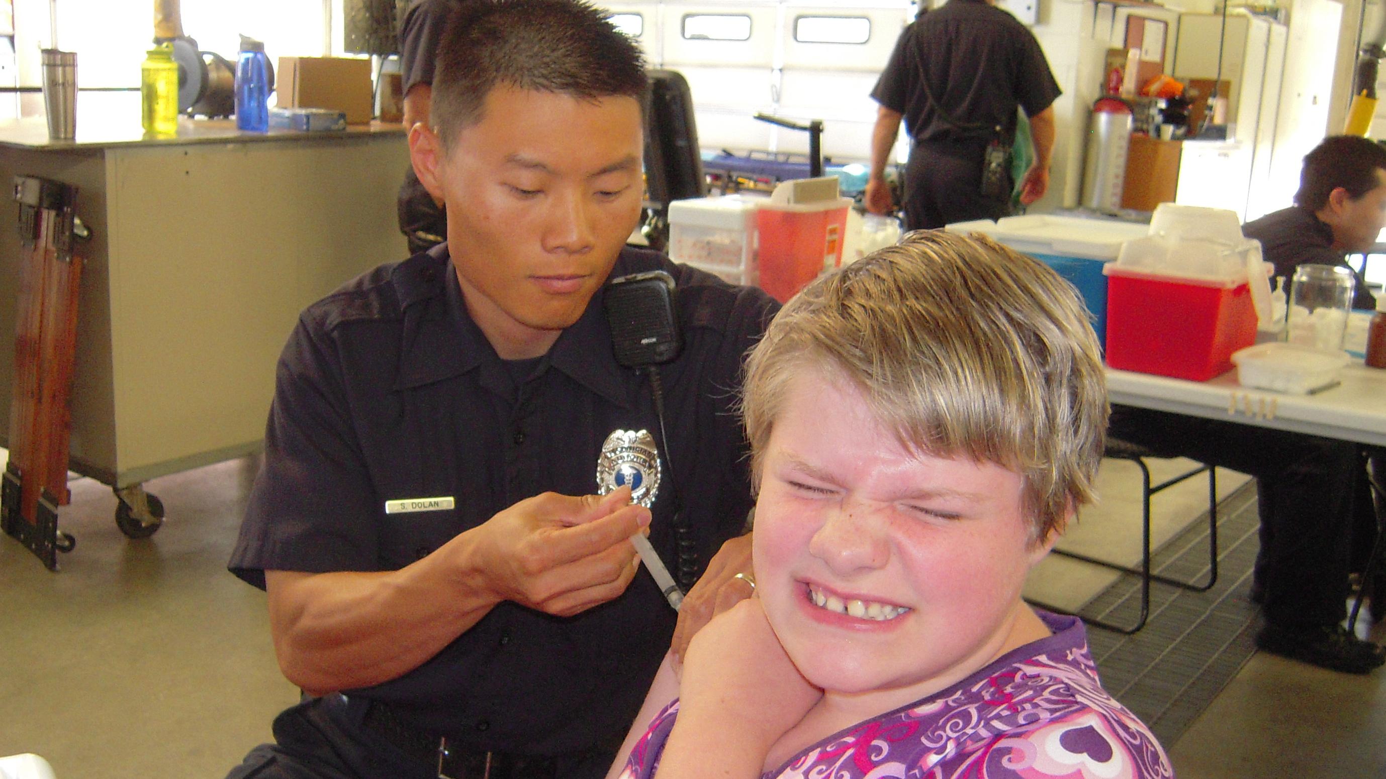 Kara Robinson, 11, received an immunization shot from Aurora fireman Sean Dolan at the Shots for Tots immunization clinic in 2011.