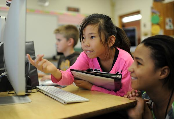 Lucky Bayar, 8, left, and Tanya Pezin, 11, check their computer project at Ellis Elementary School.