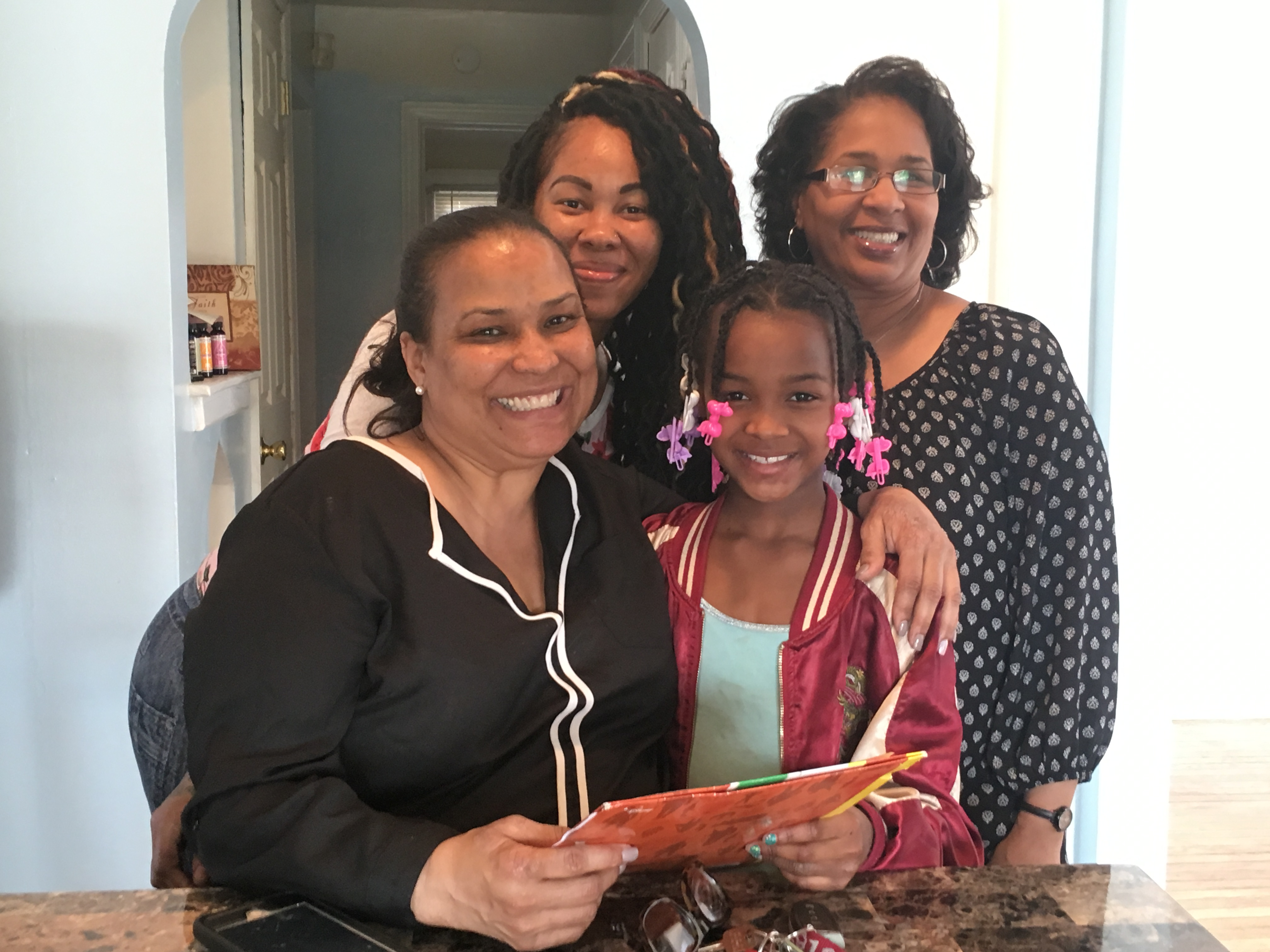 """Coleman A. Young Elementary School Principal Melissa Scott (left) and teacher Melanie Wallace (right) paid a visit to the home of Brenda Hutchins and her daughter Samantha Hutchins to discuss ways the school can help the family succeed. """"We see how hard you're working, mama!"""" Scott told her."""