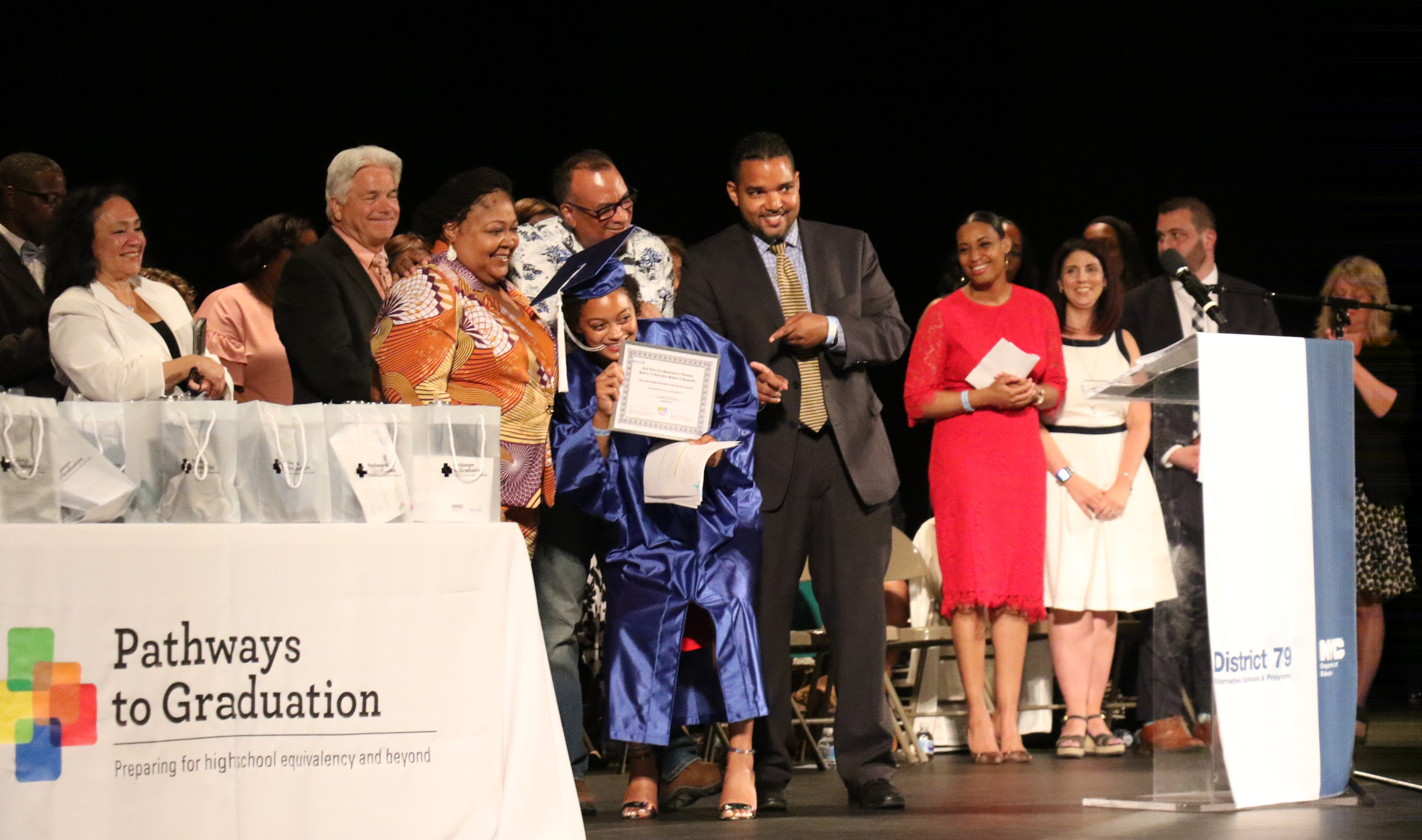 Jasmine Byrd receives an award for excellence after giving a speech to her fellow graduates.