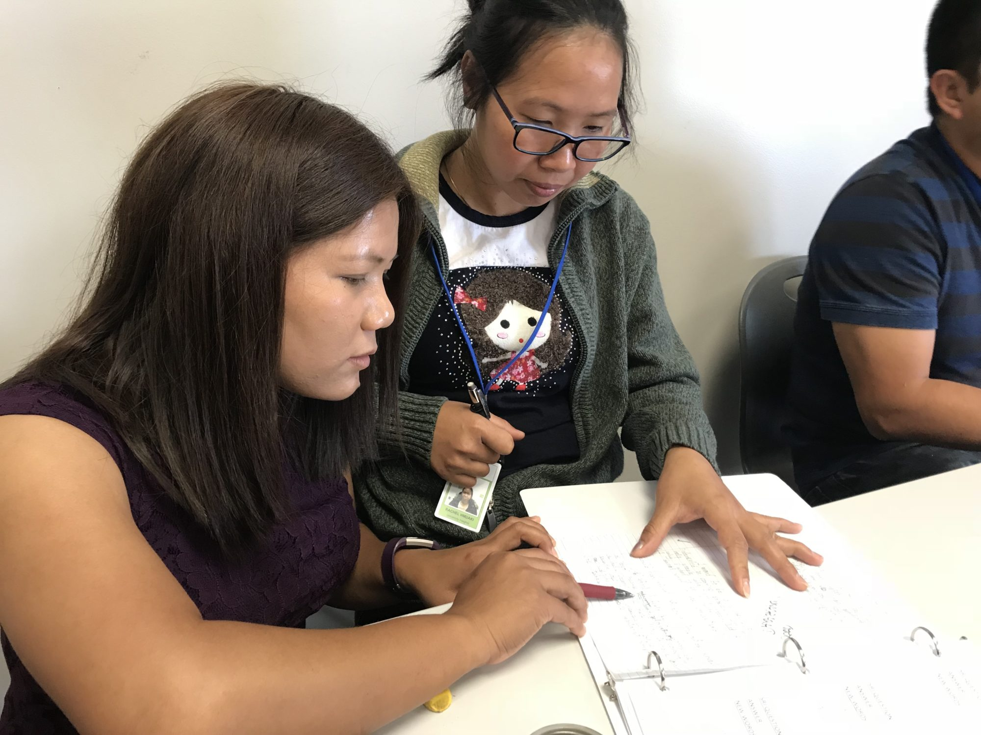 Pency Engmawii revises Rachel Hmuaki's paragraph during an English 2 class Wednesday. Engmawii left her Burmese village in Myanmar to pursue an education in the United States.