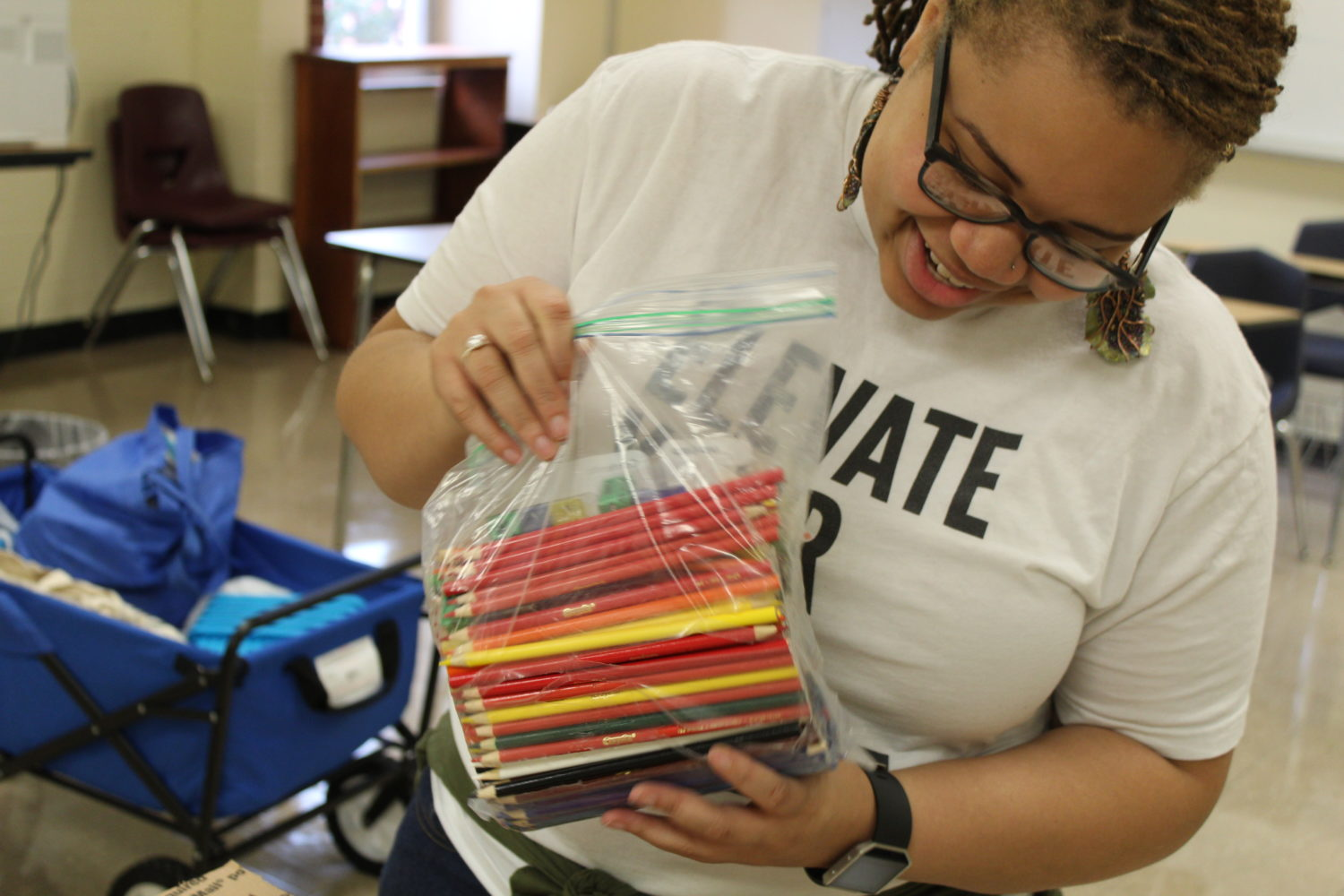 Shemena Shivers, a ninth grade science teacher at Melrose High School, smiles as she opens a package from a friend in Arizona. Through social media, Shivers has raised $1600 for her classroom.