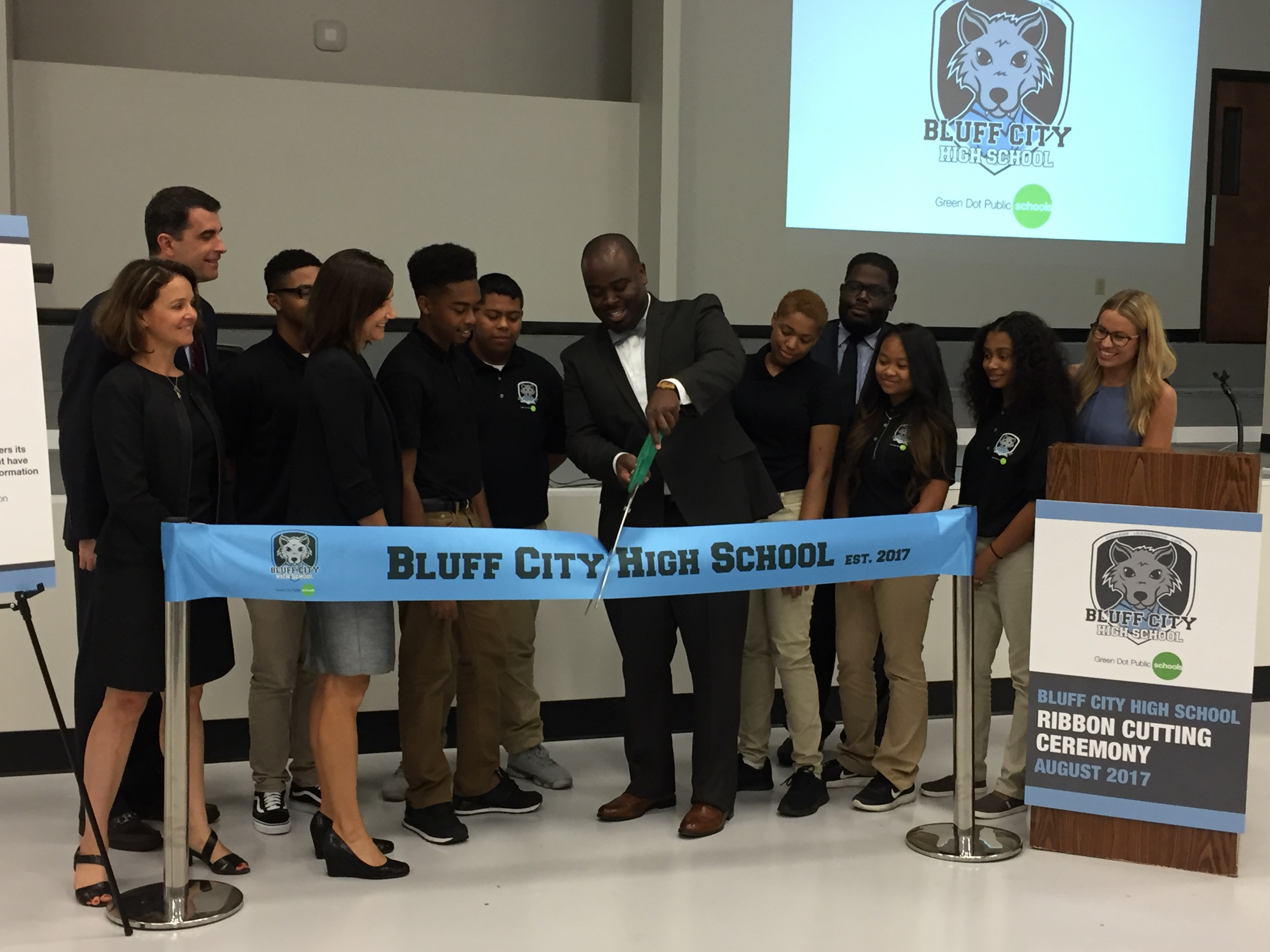 Principal Jonas Cleaves cuts the ribbon at Bluff Hills High School's opening day ceremony. He is surrounded by students, faculty and leaders of Green Dot and the State Board of Education.