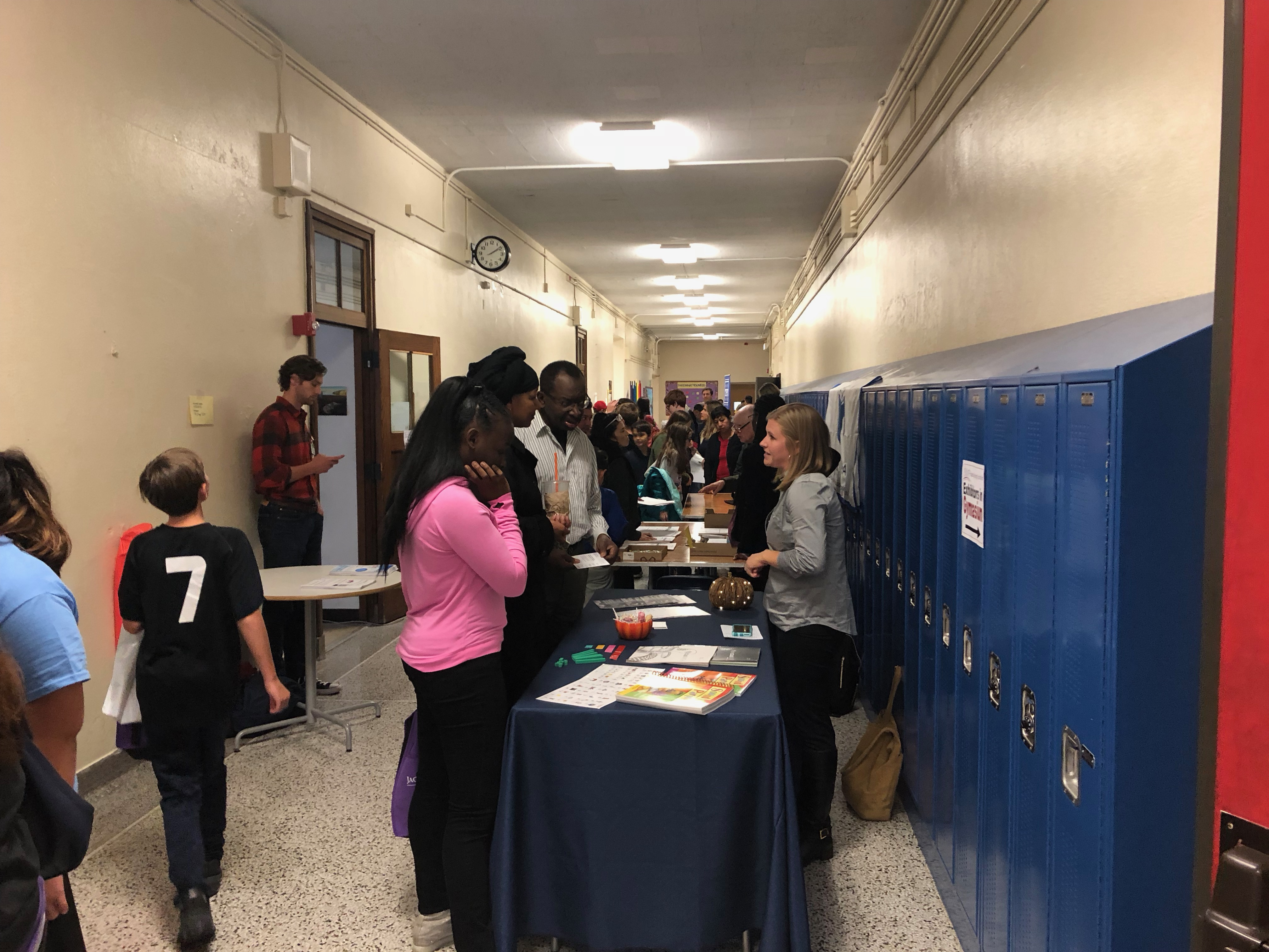 Students speak with school representatives in the hallway of Disney II Magnet High School during a high school admissions fair.