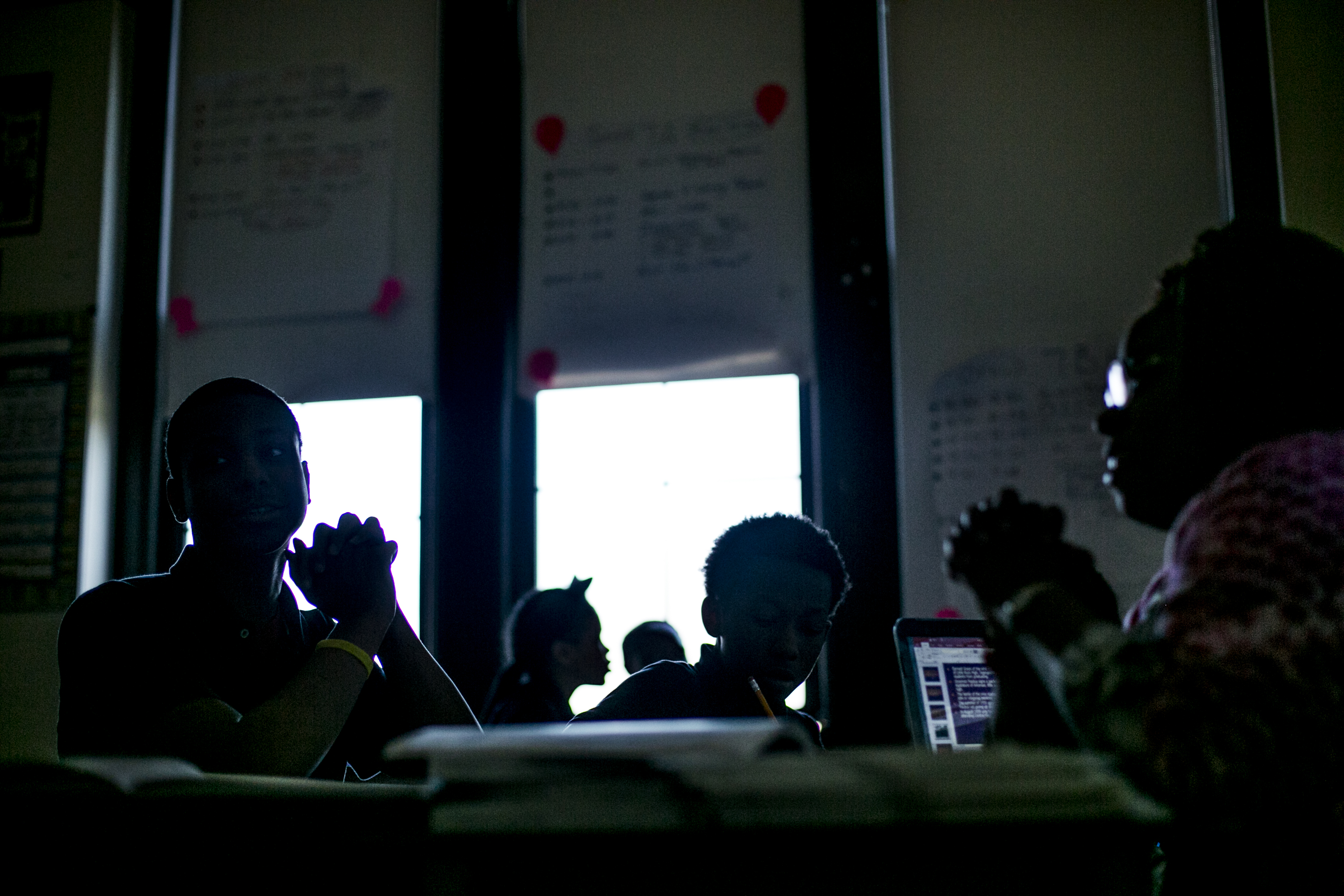 Students and their teacher sit in a dark classroom, the students silhouetted against the windows.