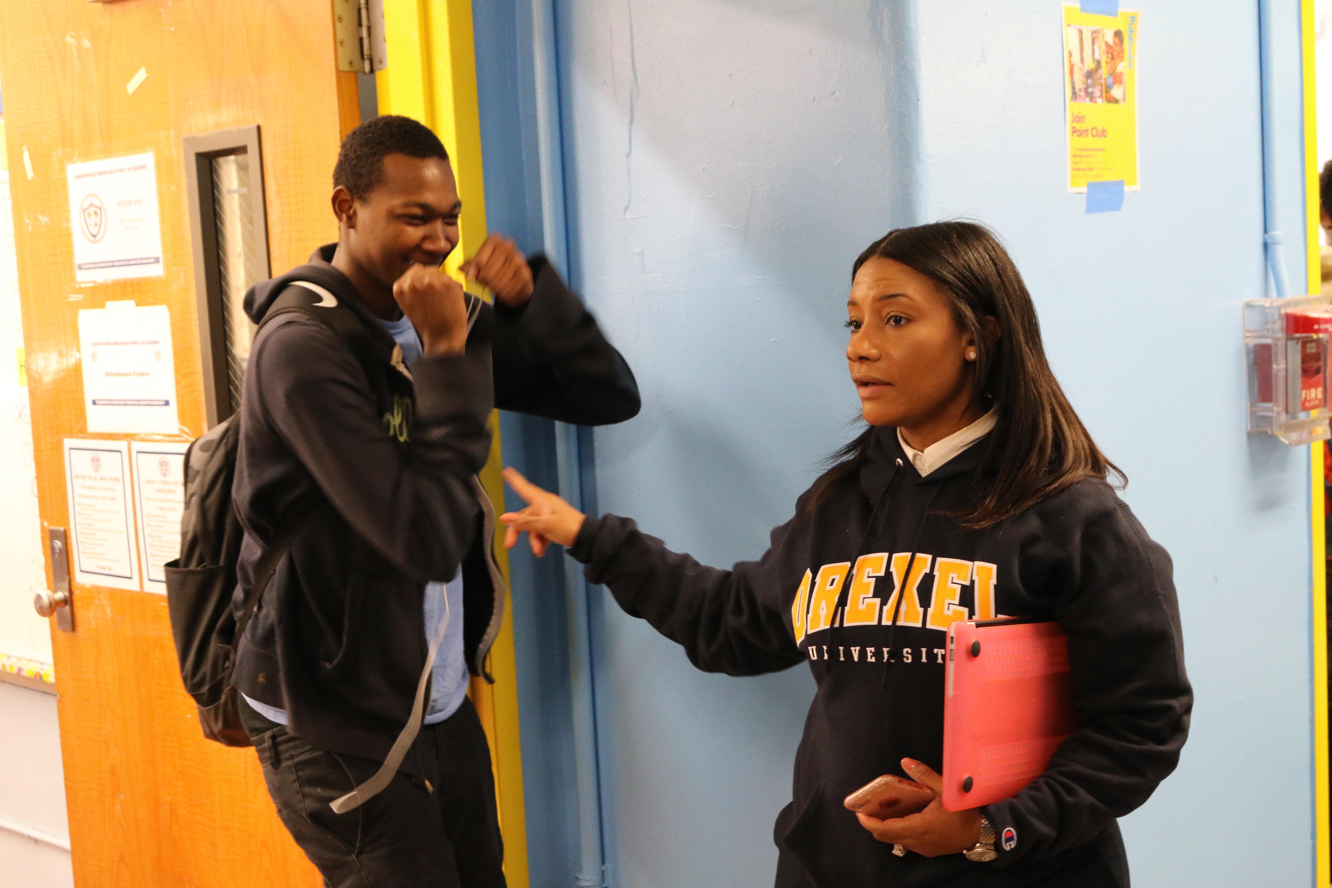 Principal Asya Johnson of Longwood Preparatory Academy, a community school, corrals a student between classes.
