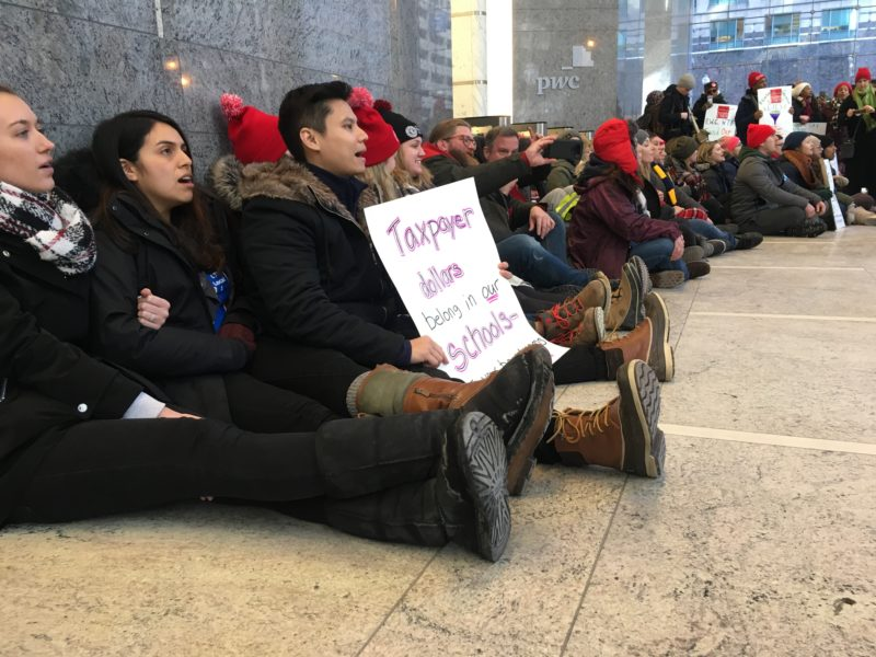 Striking educators from four Chicago International Charter School campuses on Feb. 13, 2019, block a bank of elevators at Pwc, where the charter network's president, Laura Thonn, works.