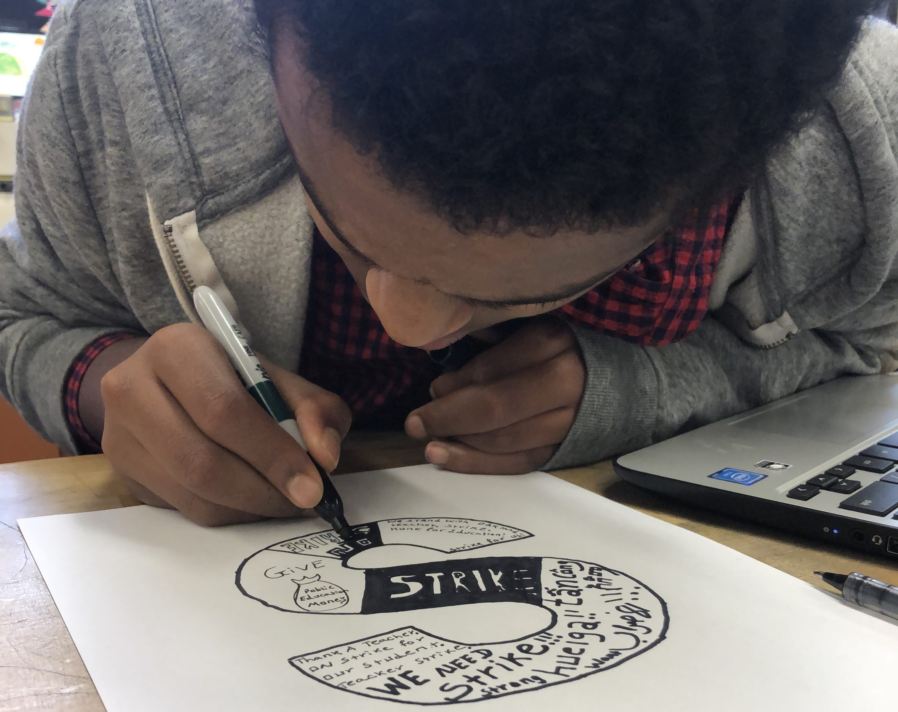 A student at Oakland International High School works on a strike-related art project, part of a lesson in the February 2019 run-up to a planned teachers strike in the Oakland Unified School District.