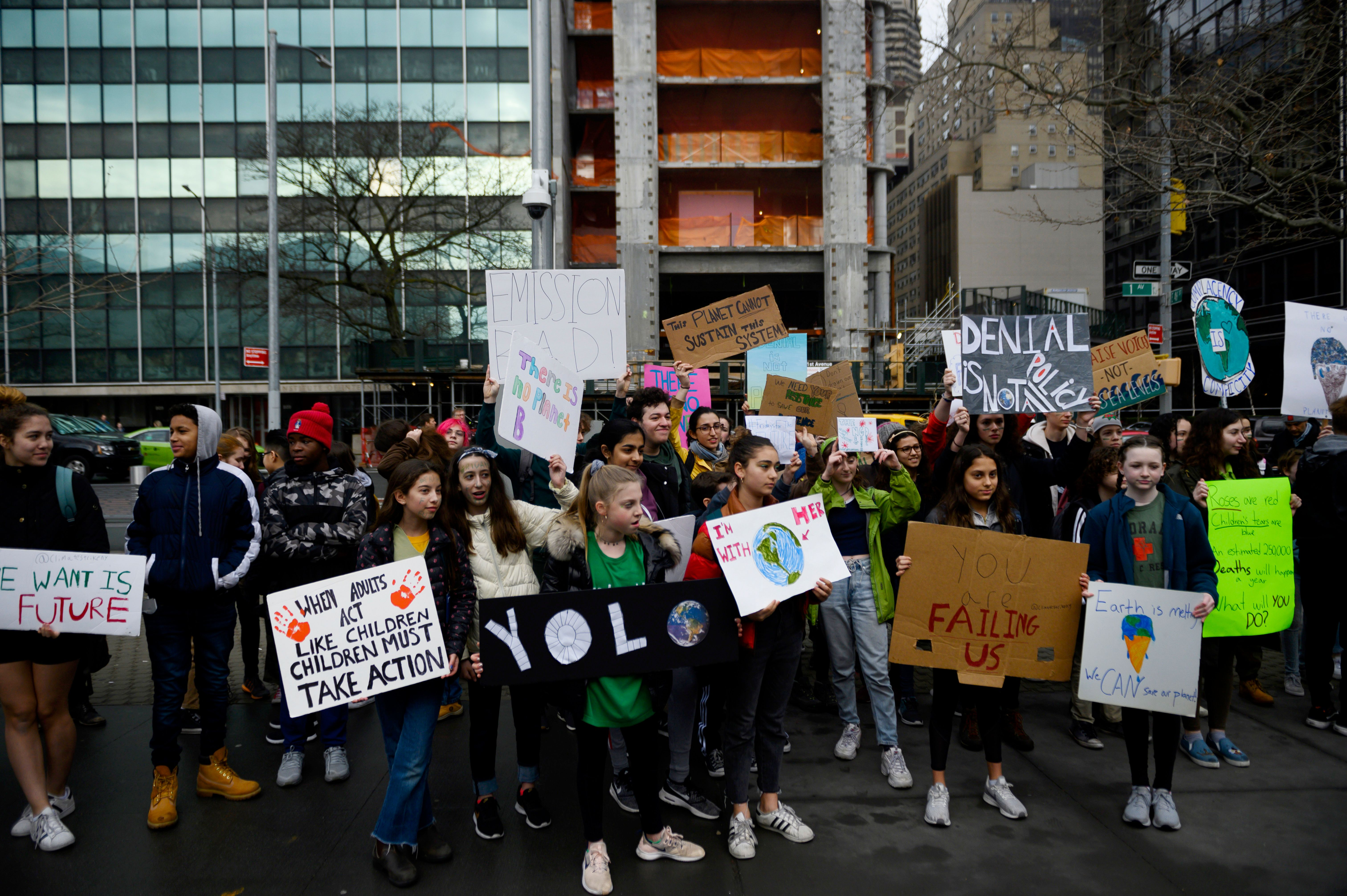 School children hold signs during a Youth Climate Strike in front of the New York Headquarters of the United Nations on March 15, 2019.