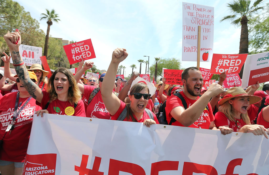 Arizona teachers chant in support of the #REDforED movement as they walk through downtown Phoenix  to the State Capitol on April 26, 2018. The walkout sought better wages and state funding for public schools. Its leaders are talking with teachers in Tennessee about how they can organize in a similar fashion. (Photo by Ralph Freso/Getty Images)