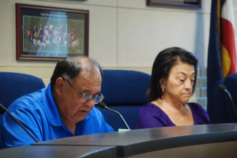 A man wearing glasses in a blue shirt and a woman also wearing a blue shirt sit at a table. Both are looking down.