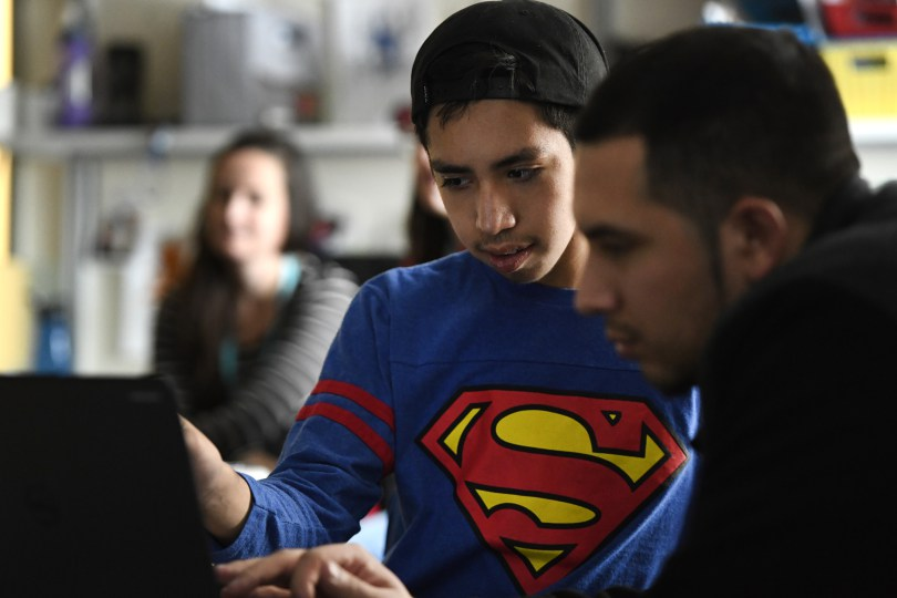Josue Bonilla, 13, middle, works on the computer with his older brother Daniel, 23, right, who came to visit Josue in his special education class at Strive Prep on December 20, 2016 in Denver, Colorado.