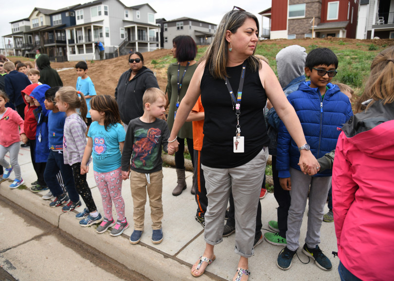 Students were escorted to school buses in front of STEM School Highlands Ranch after the shooting there.