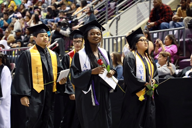 Avid students at Harrison High School's 2019 graduation ceremony stand proudly after receiving their diplomas.