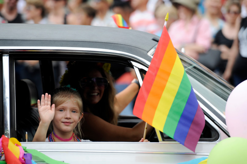 A child waves a a rainbow flag out of a window during the Denver Pride Parade along Colfax Avenue in 2018.