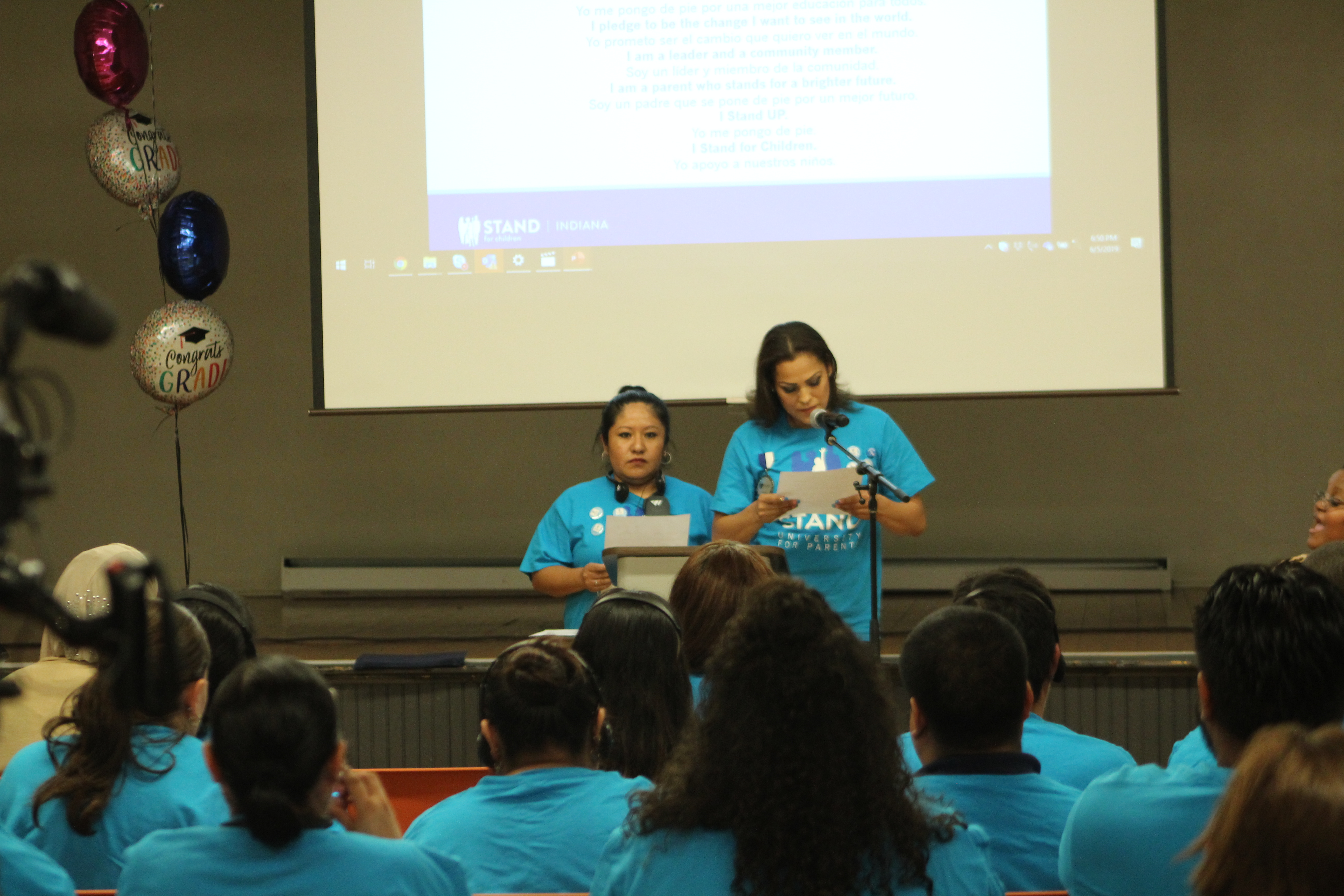 Stand UP parents Edith Aguilar and Angelina Olmedo read their organization's pledge at a graduation ceremony Wednesday.
