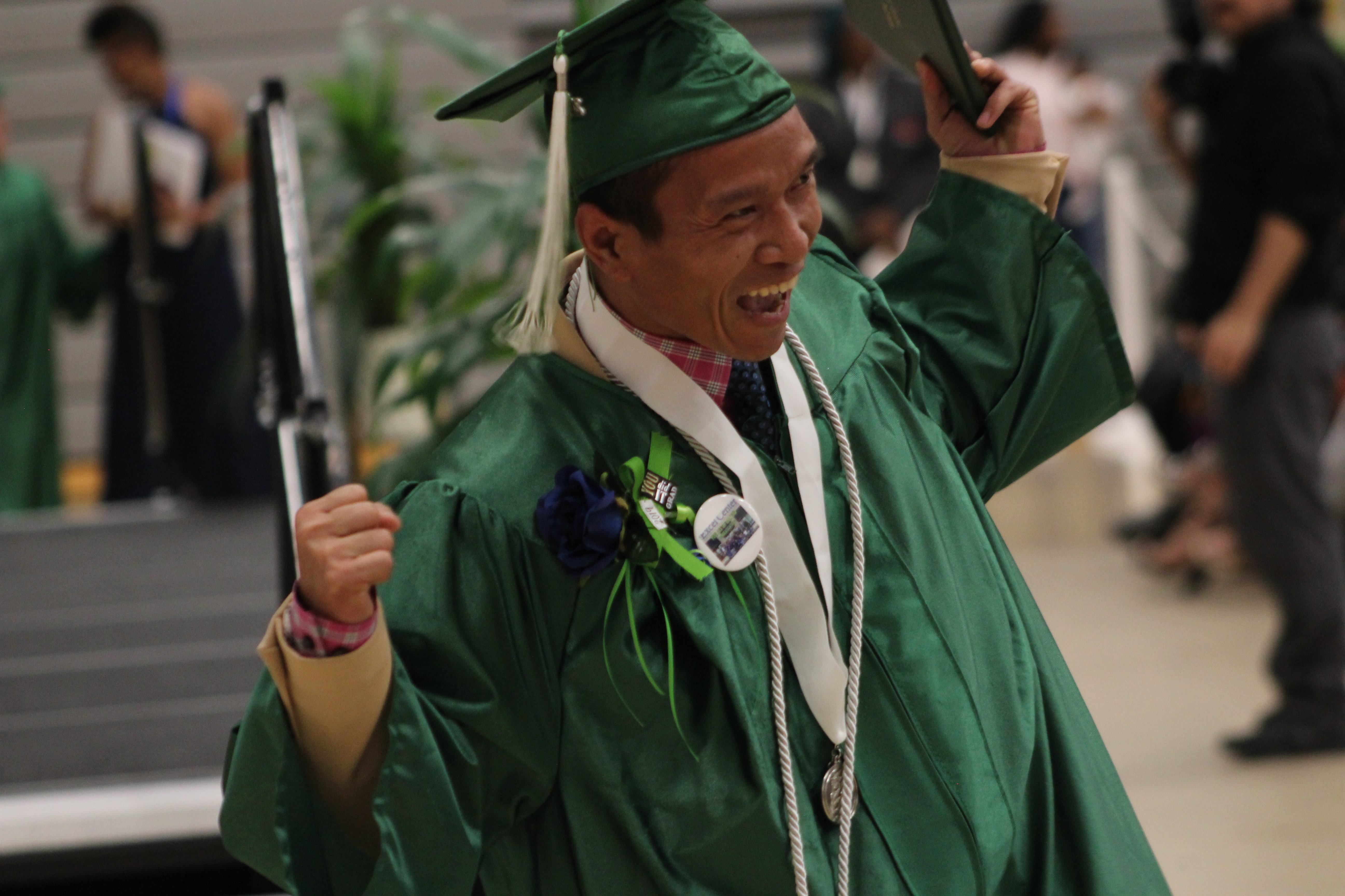 An Excel Center graduate celebrates after crossing the stage at a ceremony Thursday night.