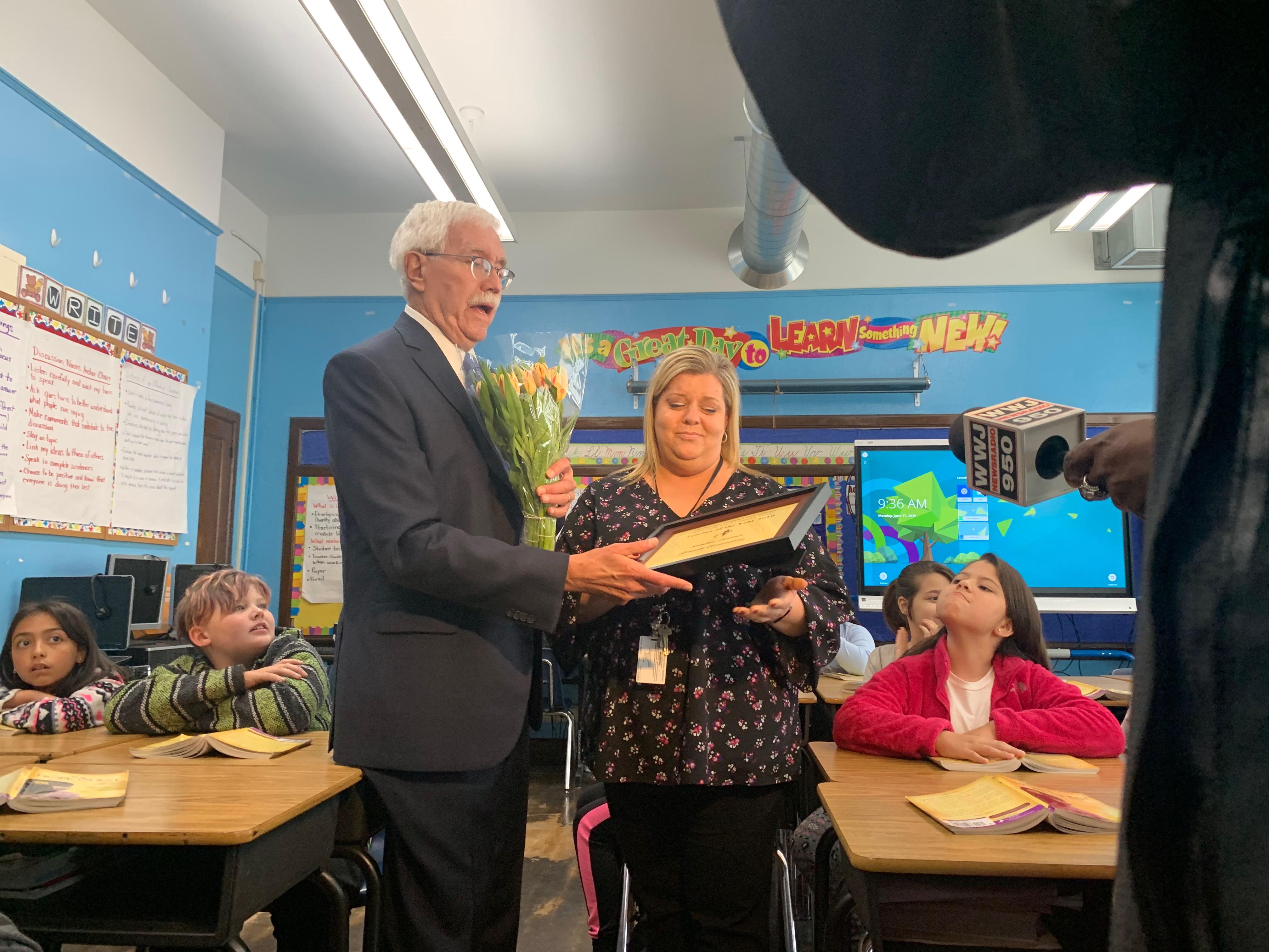 Detroit Goodfellows President Marshall Hunt presents Sandra Limmer with the Teacher of the Year award.