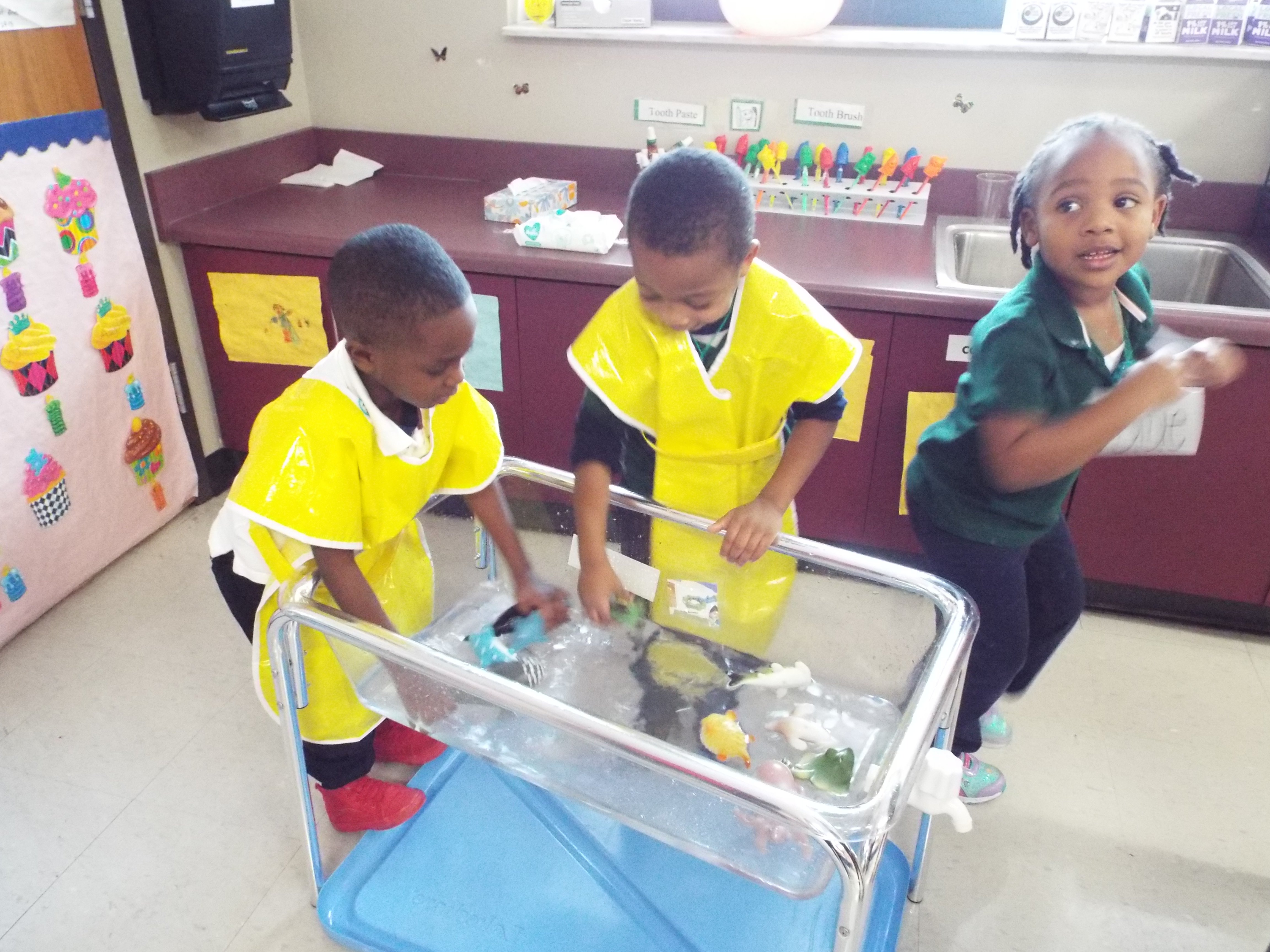 """Two boys splash in the """"ocean,"""" a large aquarium-like container half-filled with water and tiny plastic sea creatures, in a prekindergarten class at Lucie E. Campbell Elementary in Memphis."""