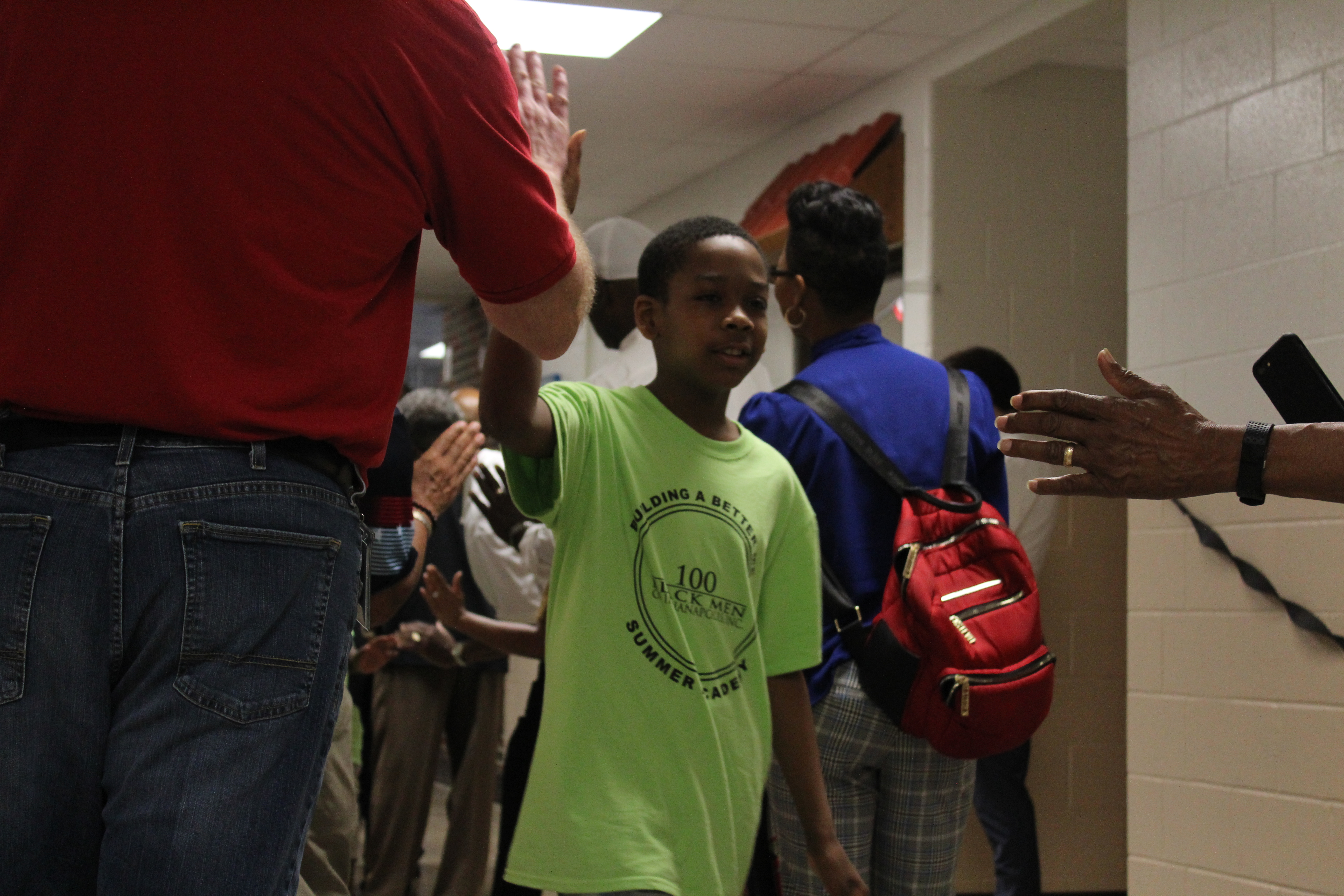 Community members and organizers with the 100 Black Men of Indianapolis' Summer Academy welcome a student with a high-five rally.