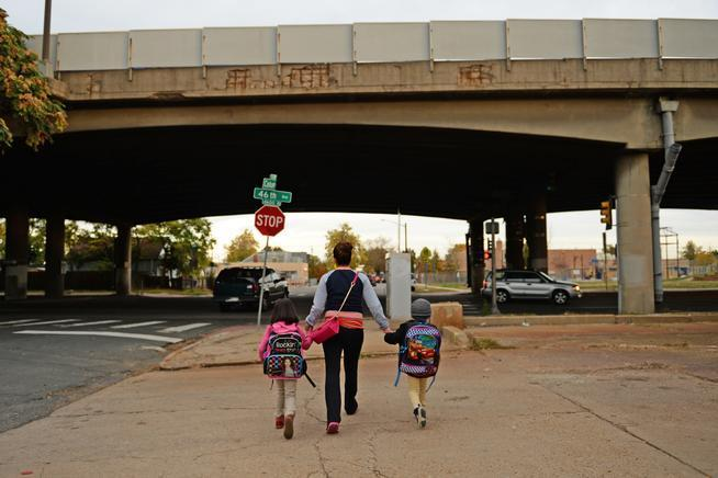 A Denver mother walks her children to Swansea Elementary just north of I-70 in this 2014 file photo.