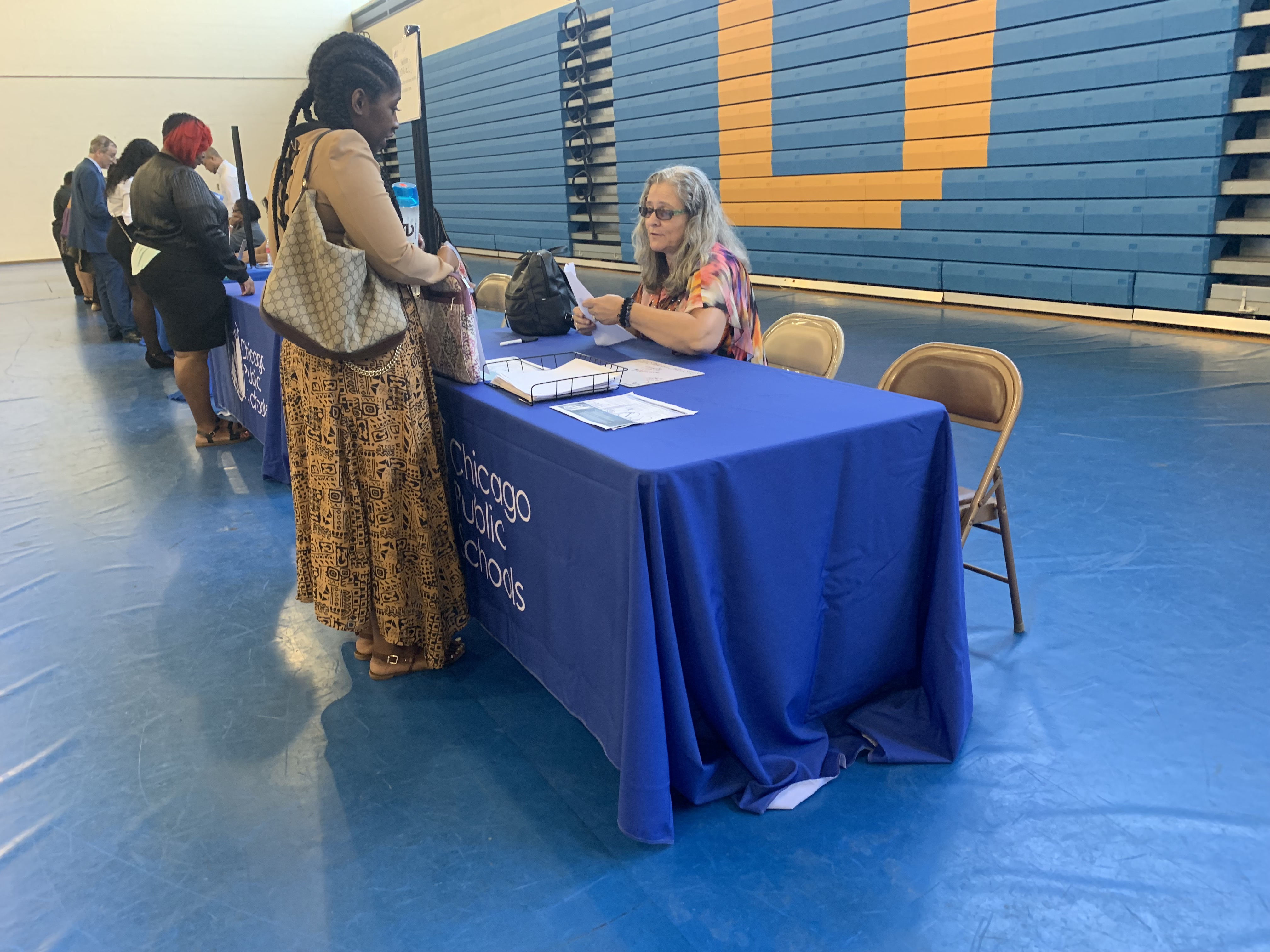 A district representative speaks to a candidate at the Chicago Public Schools job fair in the gymnasium of Richard J Daley College.