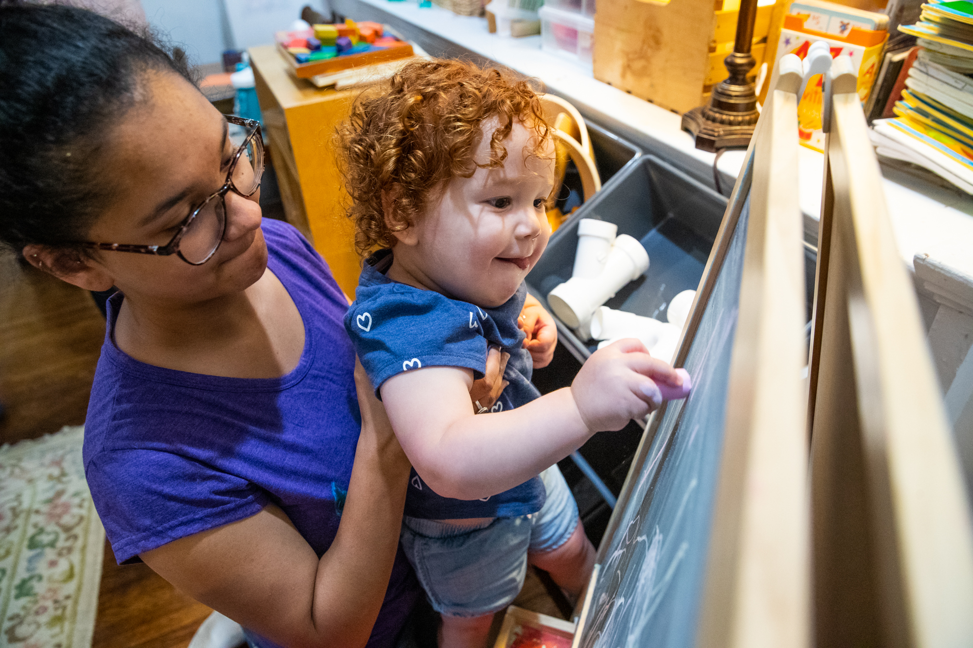 Justice Vaughn (left), daughter of Cynthia Randolph-Vaughn of Cindy's Center For Young Learners, lifts up Prose VanVeelen, 2, while coloring with chalk on Wednesday, May 29, 2019. Randolph-Vaughn runs a level 4 child care center out of her home. The children range from 8 months to 4 years old. Justice volunteers at the child care center.