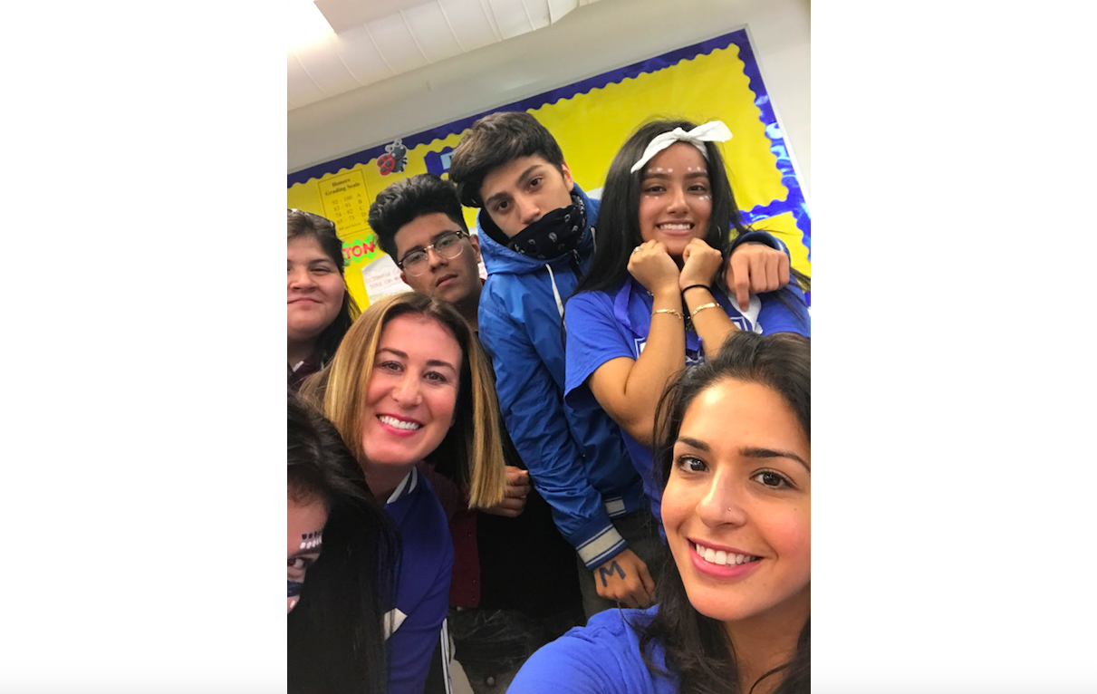 Hyam Elsaharty, bottom right, a teacher at Mather High School in Chicago, poses in 2018 with her students at homecoming.