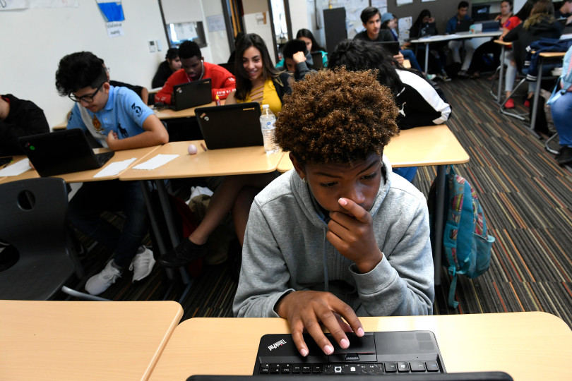 A high school student works at a computer amongst his classmates, several of which are behind him.