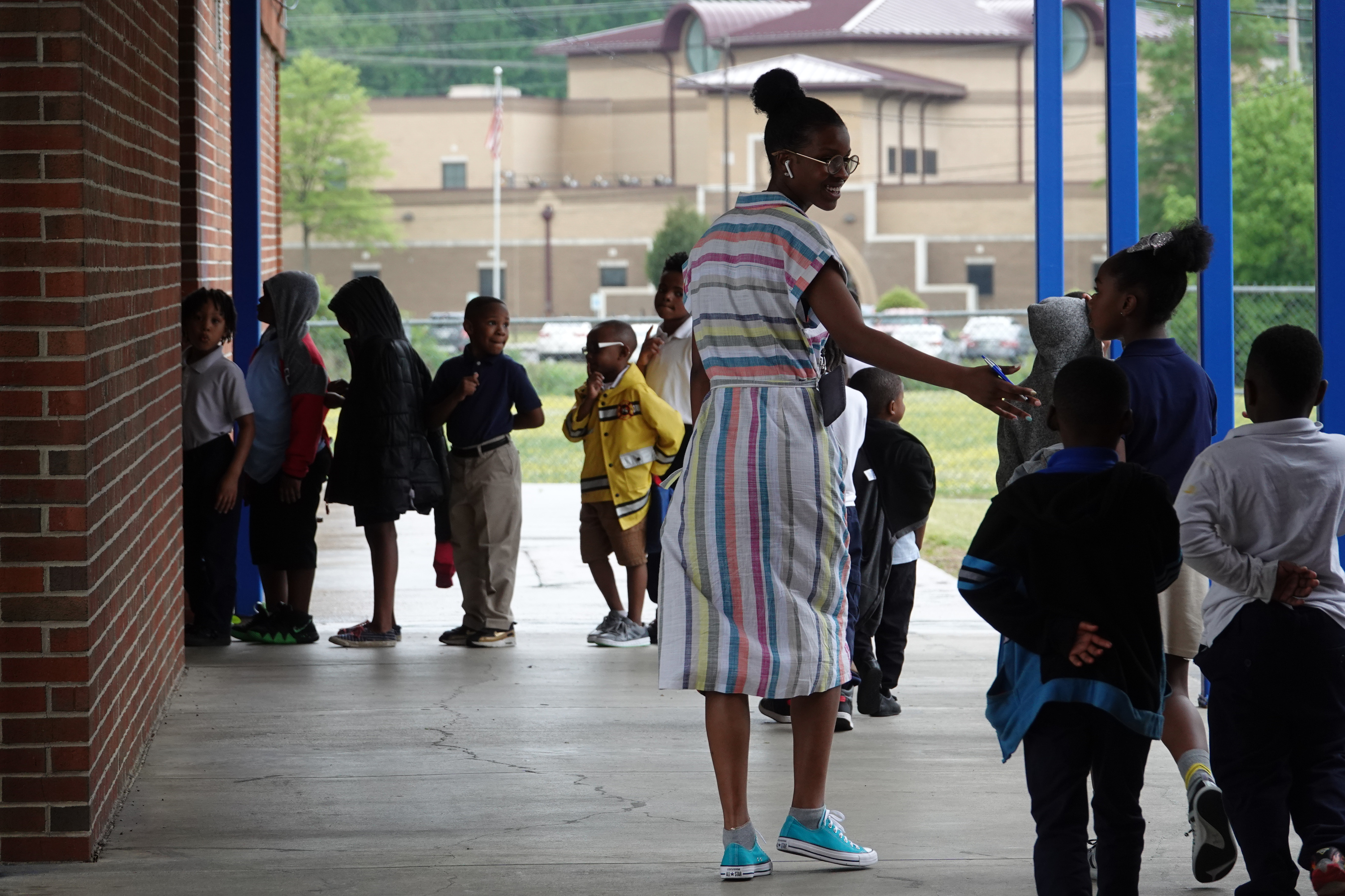 An elementary teacher walks with her student to another classroom outside.