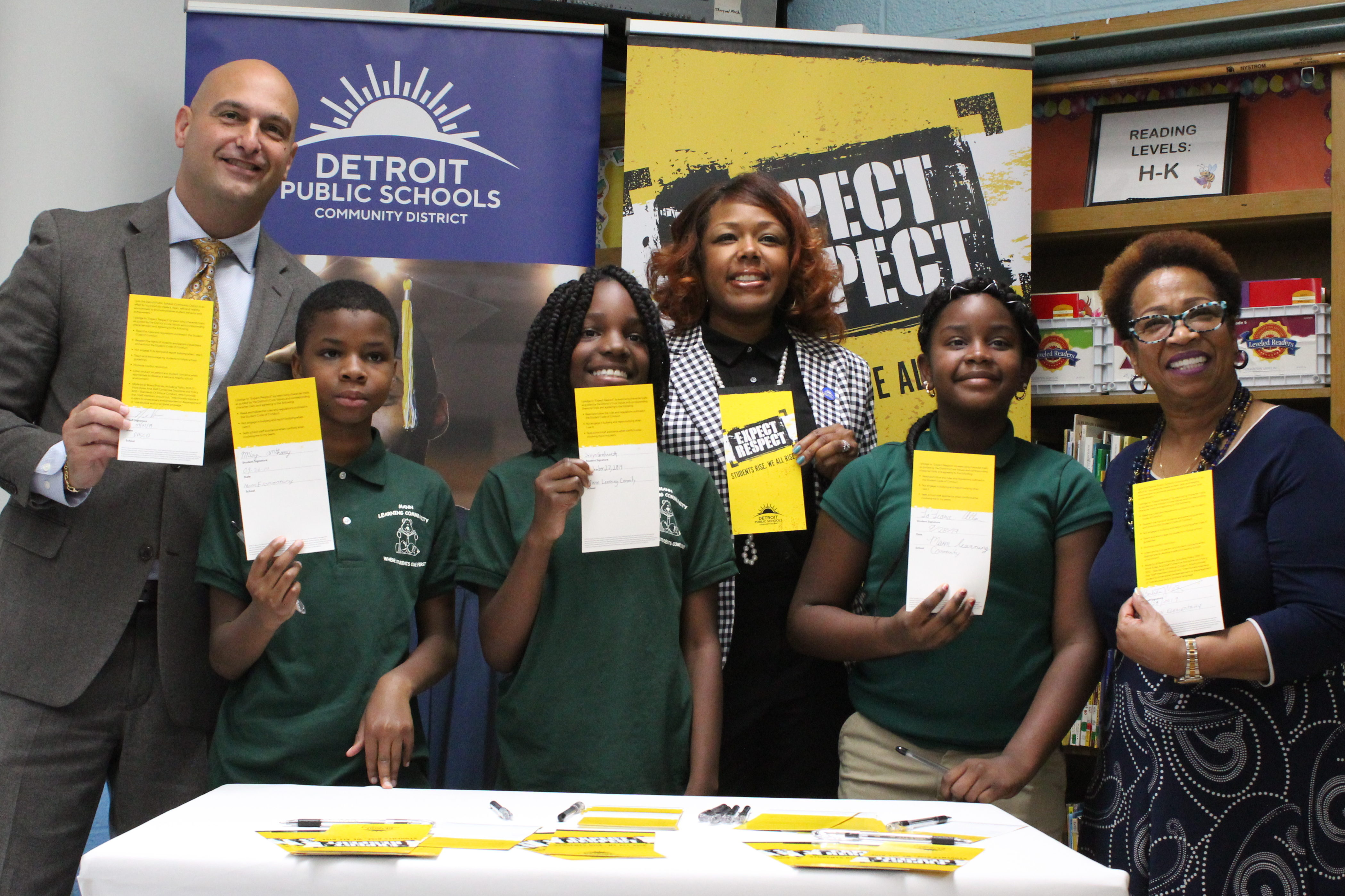 Superintendent Nikolai Vitti (left), and board members Angelique Peterson-Mayberry and Corletta Vaughn (back left and right), signed the Detroit district's new anti-bullying pledge alongside students at Mann Learning Community.