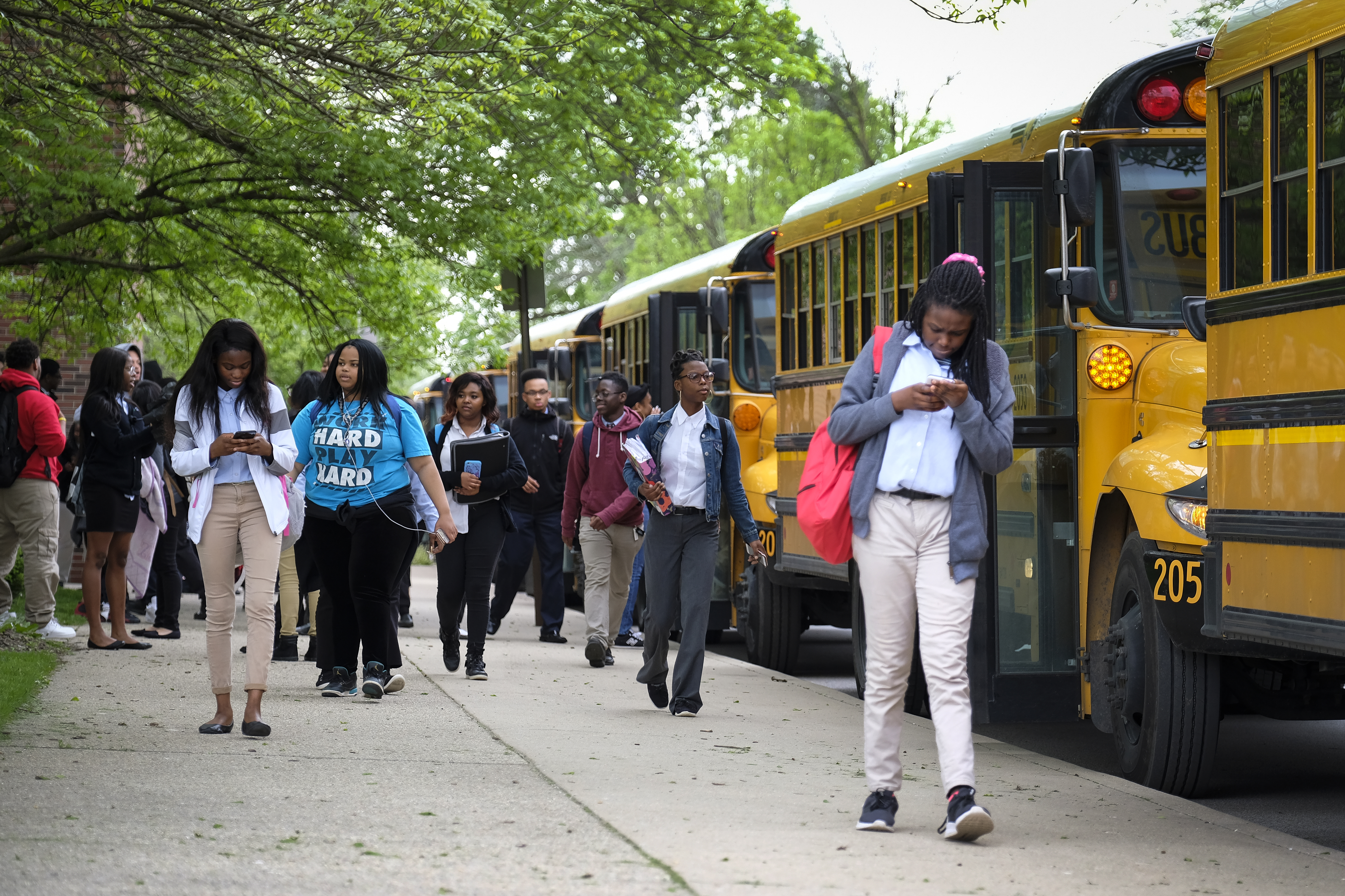 Students leave buses, on their way to classes at Providence Cristo Rey High School, a private, Roman Catholic high school in Indianapolis, Indiana. — May, 2019 — Photo by Alan Petersime/Chalkbeat