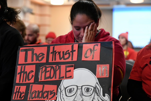 Valerie Lovato, a first grade teacher at Eagleton Elementary School, listens to continued contract negotiations on day two of the Denver teacher strike.