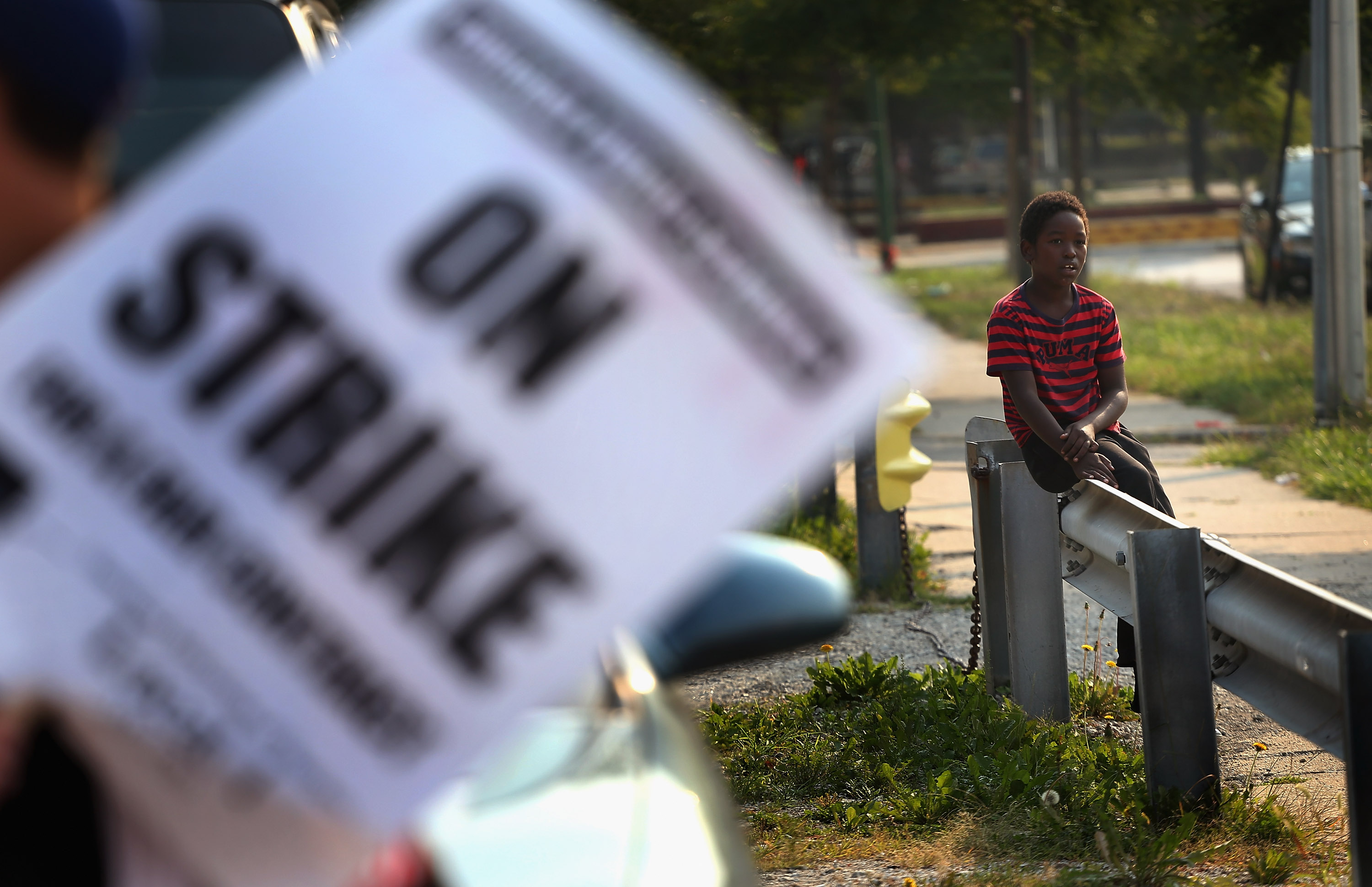 A third grader watches Chicago teachers as they picket outside his school in the fall of 2012.