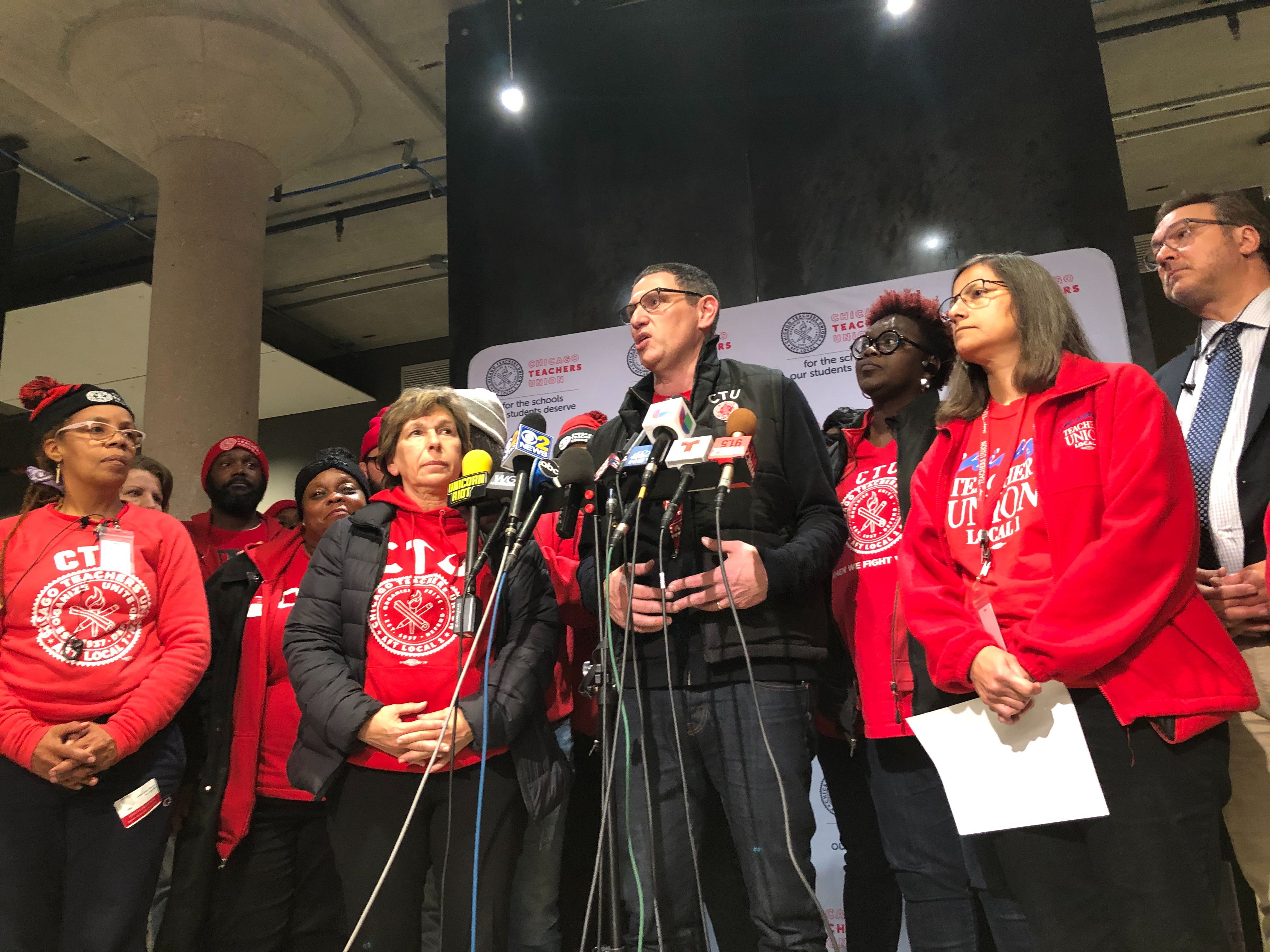 Chicago Teachers Union chief Jesse Sharkey, center, speaks to the press after a House of Delegates vote to accept a tentative contract, Oct. 30, 2019.
