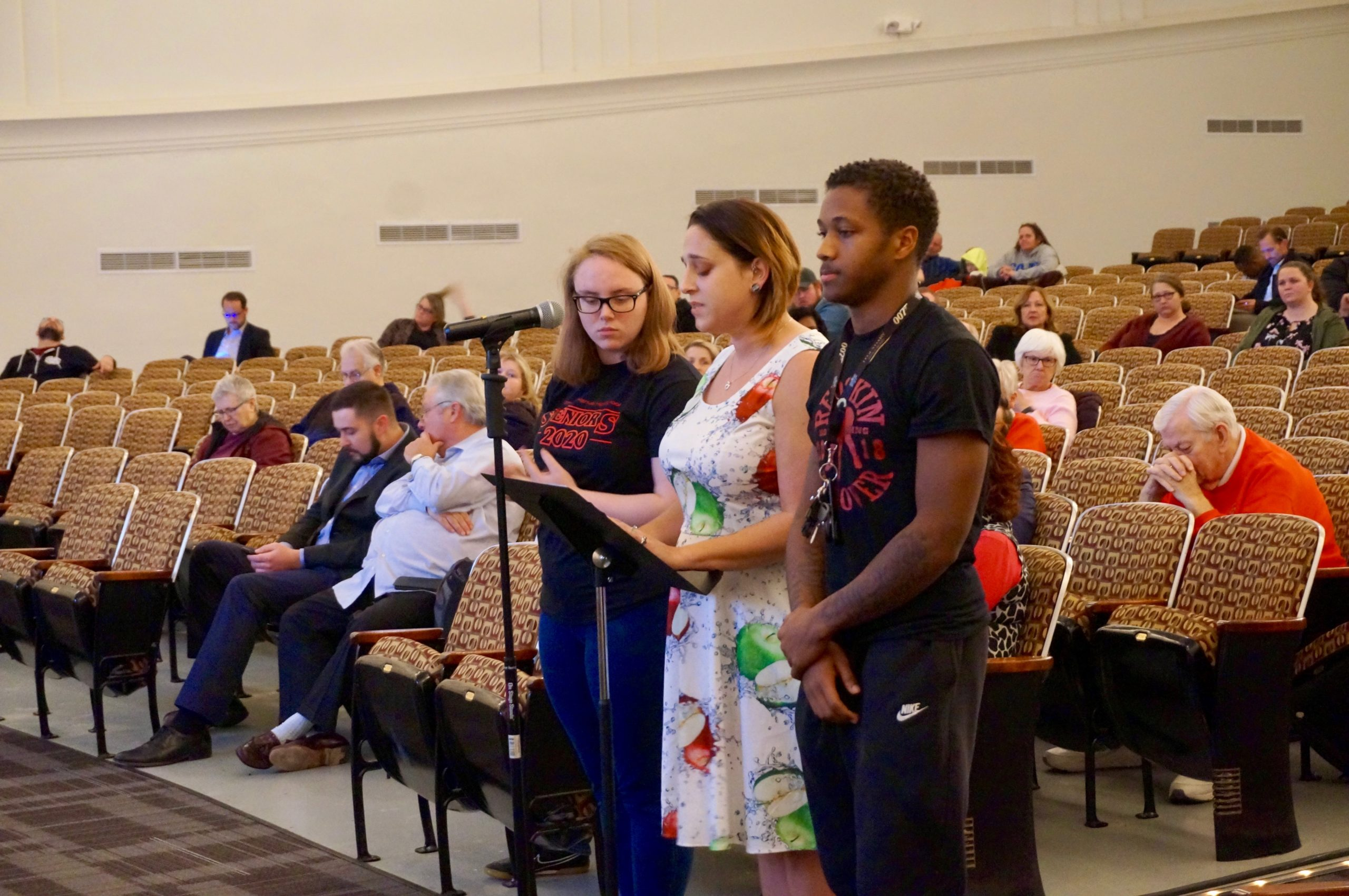 brittany yanasak, a reading specialist and English teacher from Manual High School, brought two students to the microphone as she spoke.