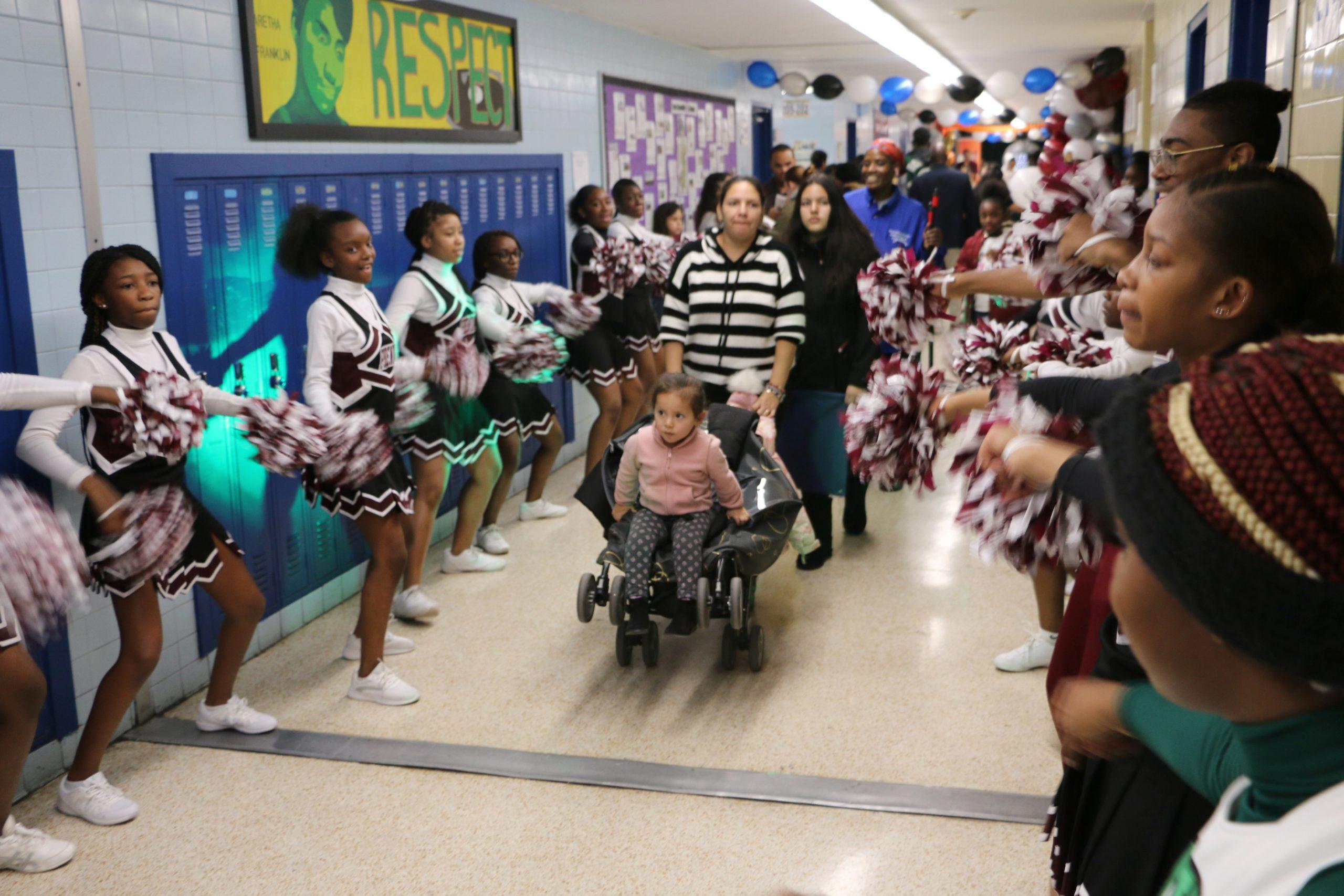 Cheerleaders from University High School greeted families at Newark's school enrollment fair on Saturday.