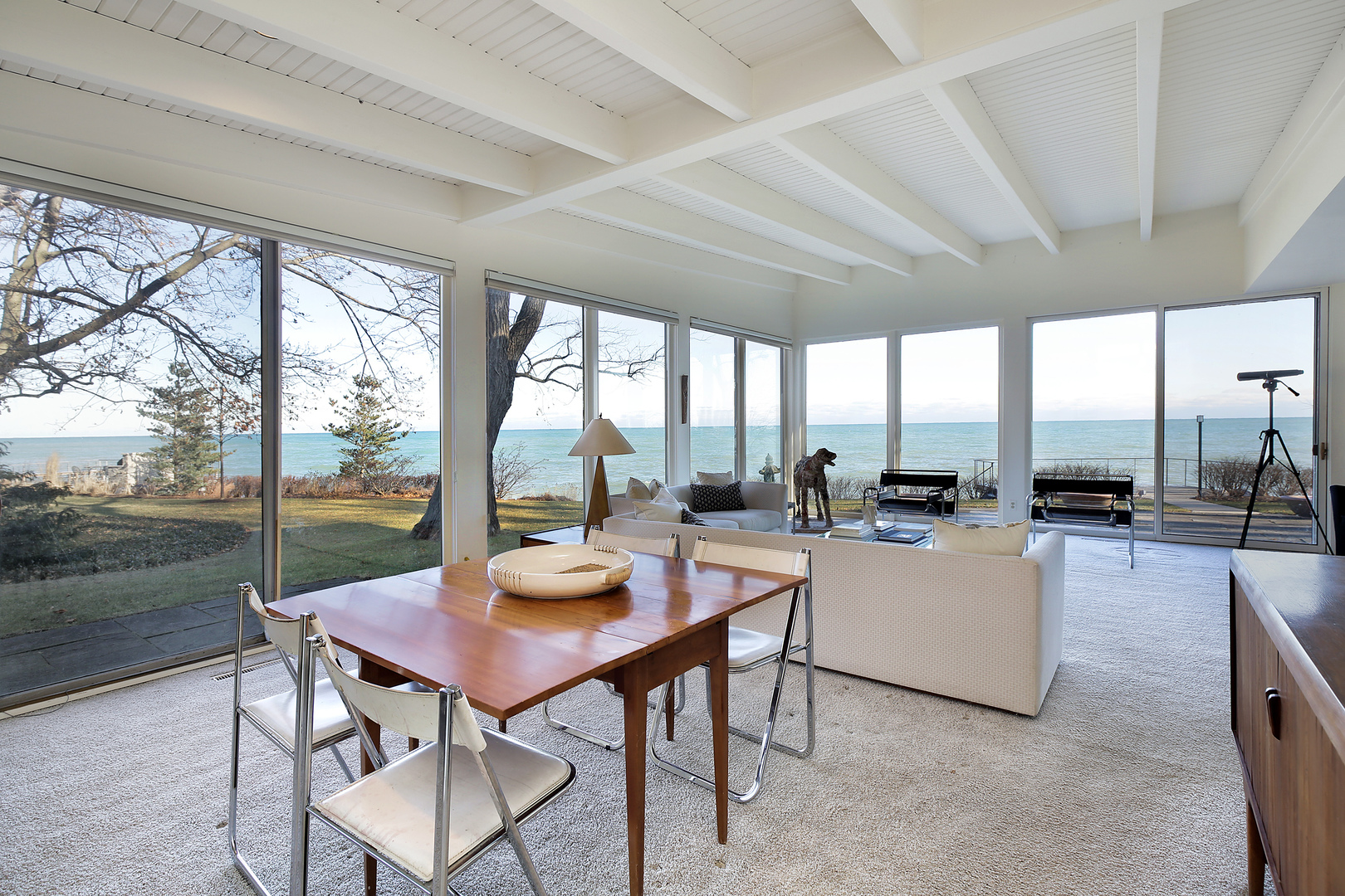 A corner living room with views of a large body of water through floor-to-ceiling windows.