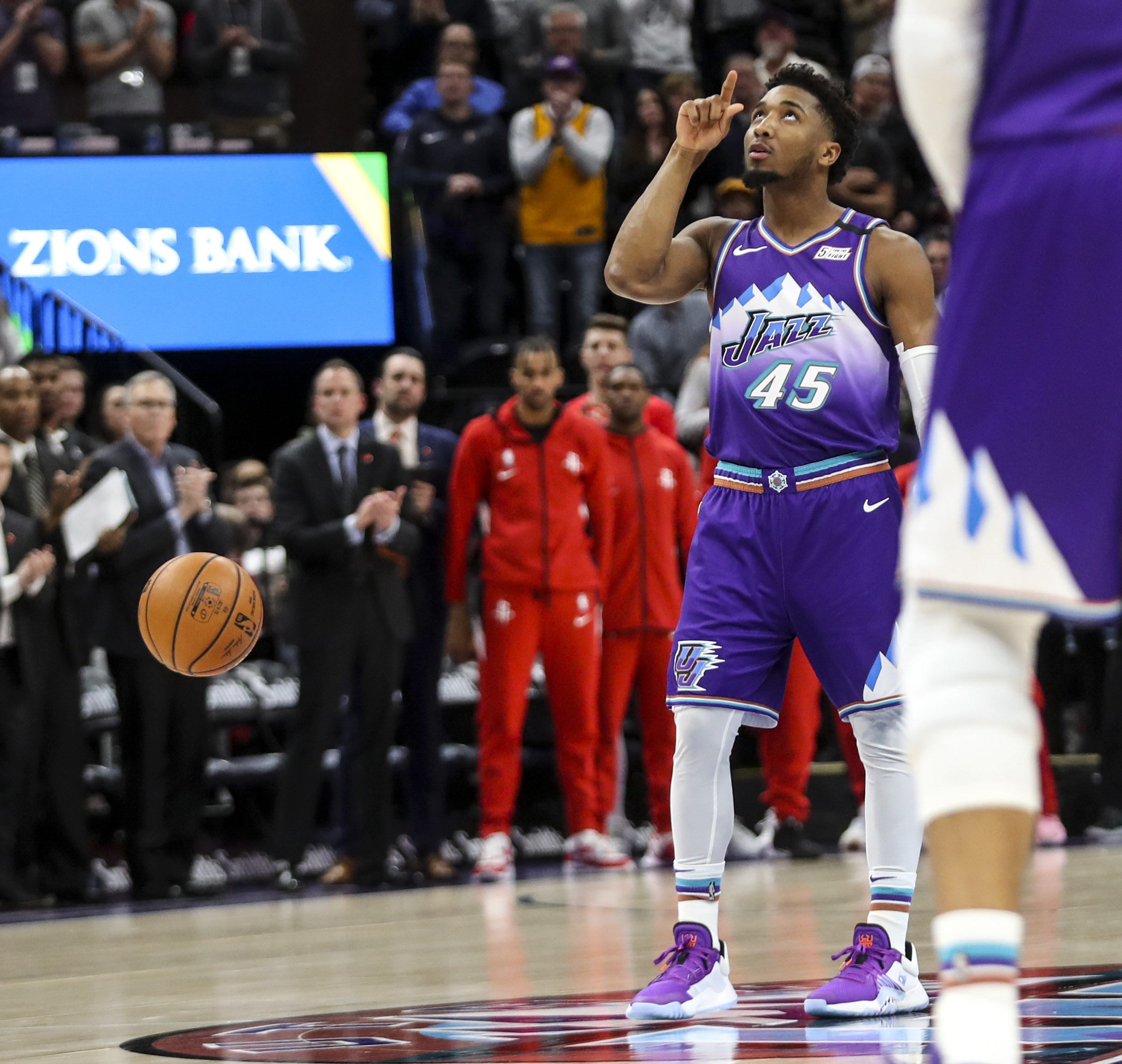 Utah Jazz guard Donovan Mitchell (45) lets the ball bounce away as he points up to the sky as the Jazz pay tribute to Kobe Bryant by letting the 24 second clock expire at the beginning of the game against the Houston Rockets at Vivint Arena in Salt Lake City on Monday, Jan. 27, 2020.