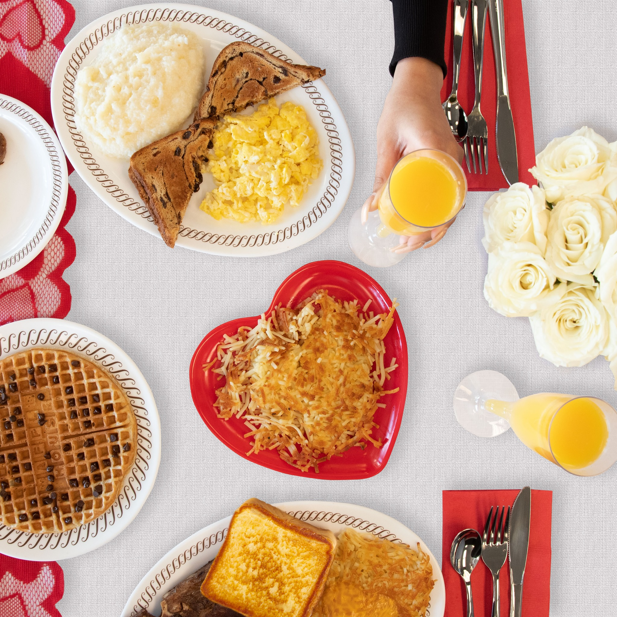 A breakfast spread with heart shaped hashbrowns, toast, eggs, white roses, and waffles for Valentine's Day at Waffle House