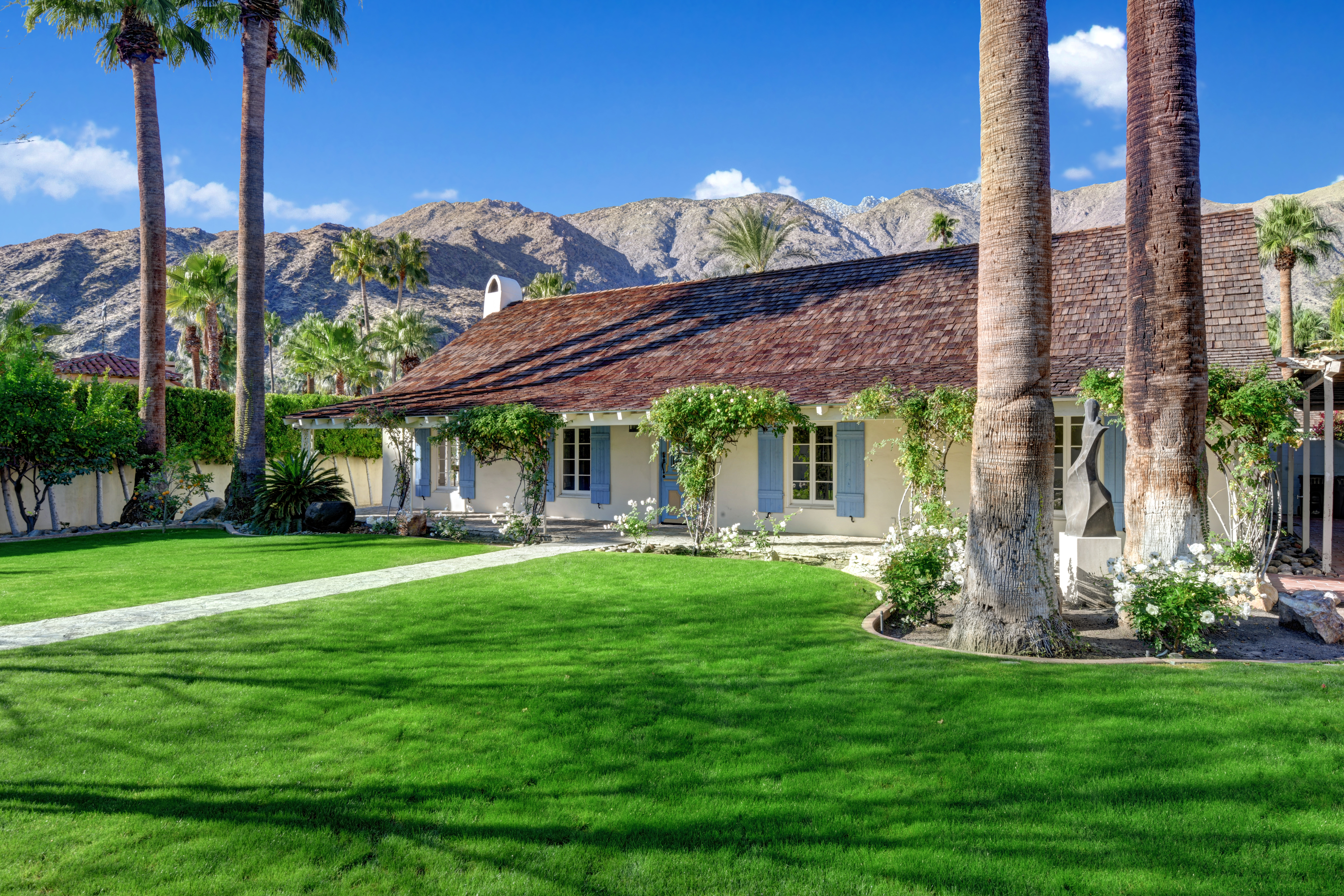A ranch house with a low-slung roof and blue shutters sits in a large grassy lawn. Palm trees are in the front and mountains behind the cottage.