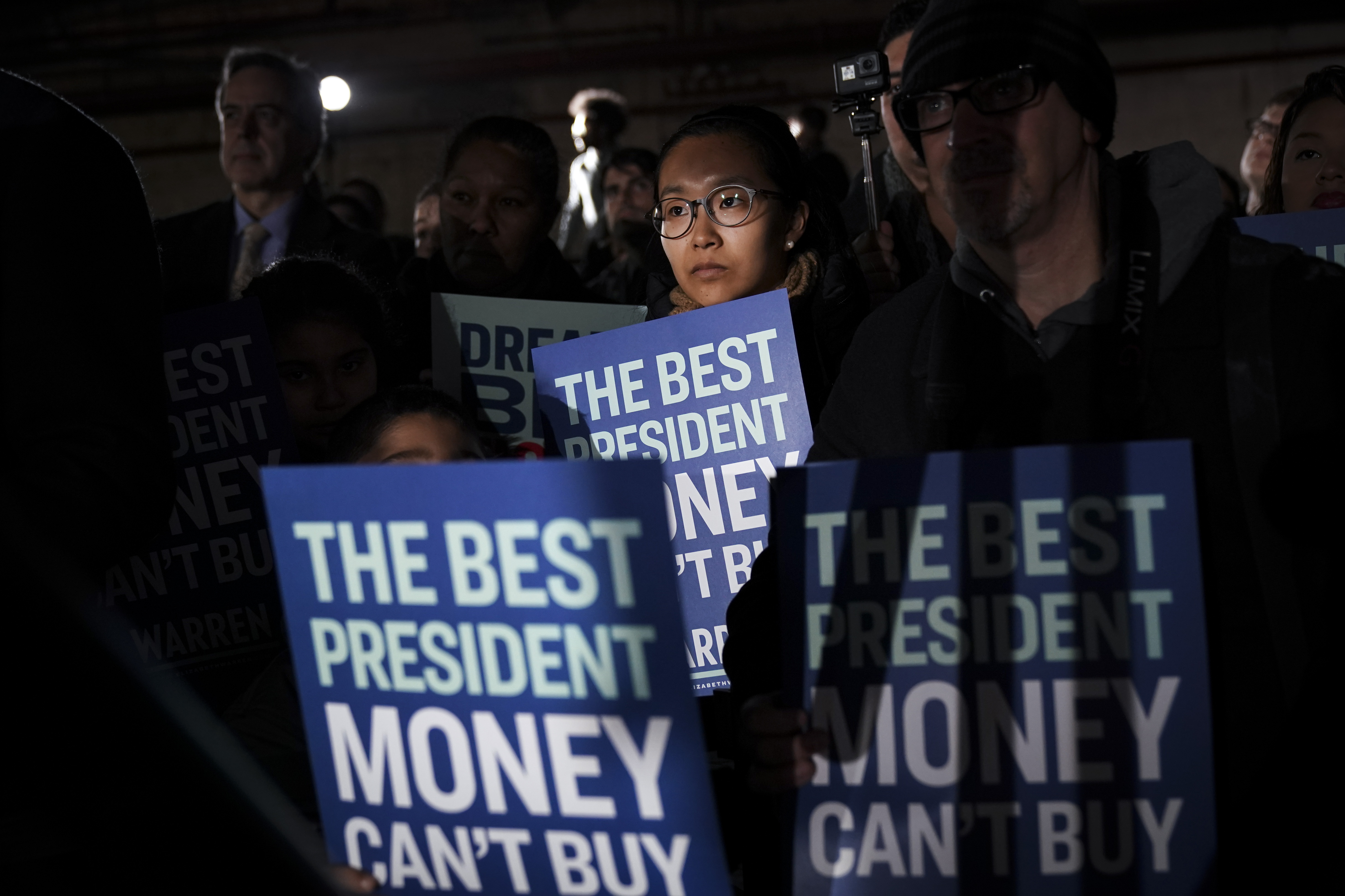 "Elizabeth Warren supporters hold signs reading ""The Best President Money Can't Buy."""