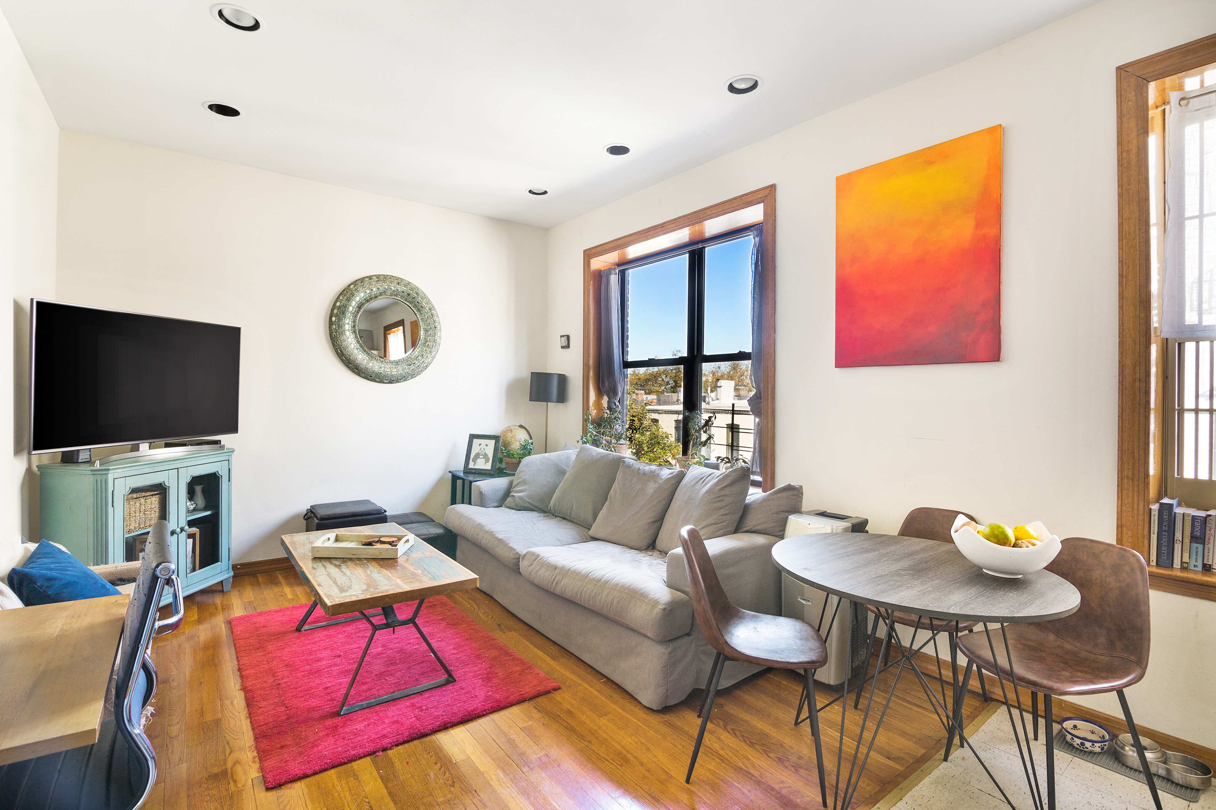 A living room with hardwood floors, a grey couch, a pink rug, a coffee table, and a round dining table with three chairs.